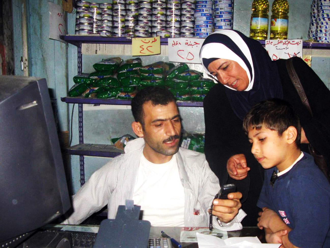 Iraqi refugees use a WFP food voucher on their mobile phone to purchase food from a shop in Damascus