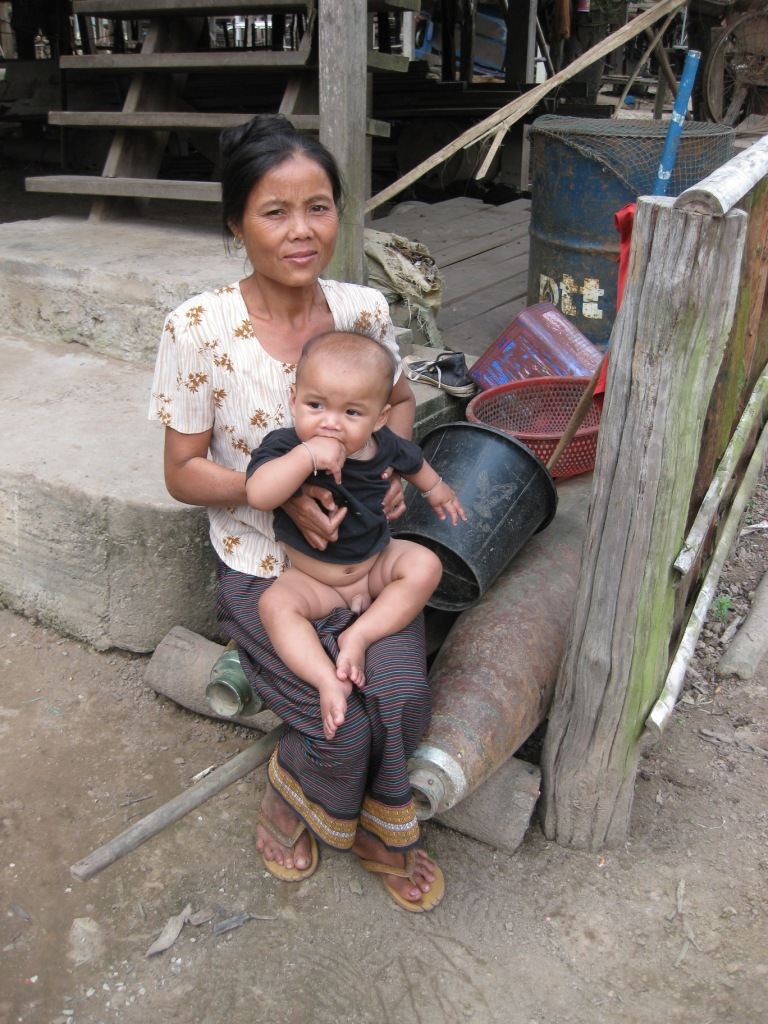 Janthan, from Phanop Village on the Ho Chi Minh trail, sits beside one of her two defused 500-pound bombs, which will be sold for scrap metal when prices rise