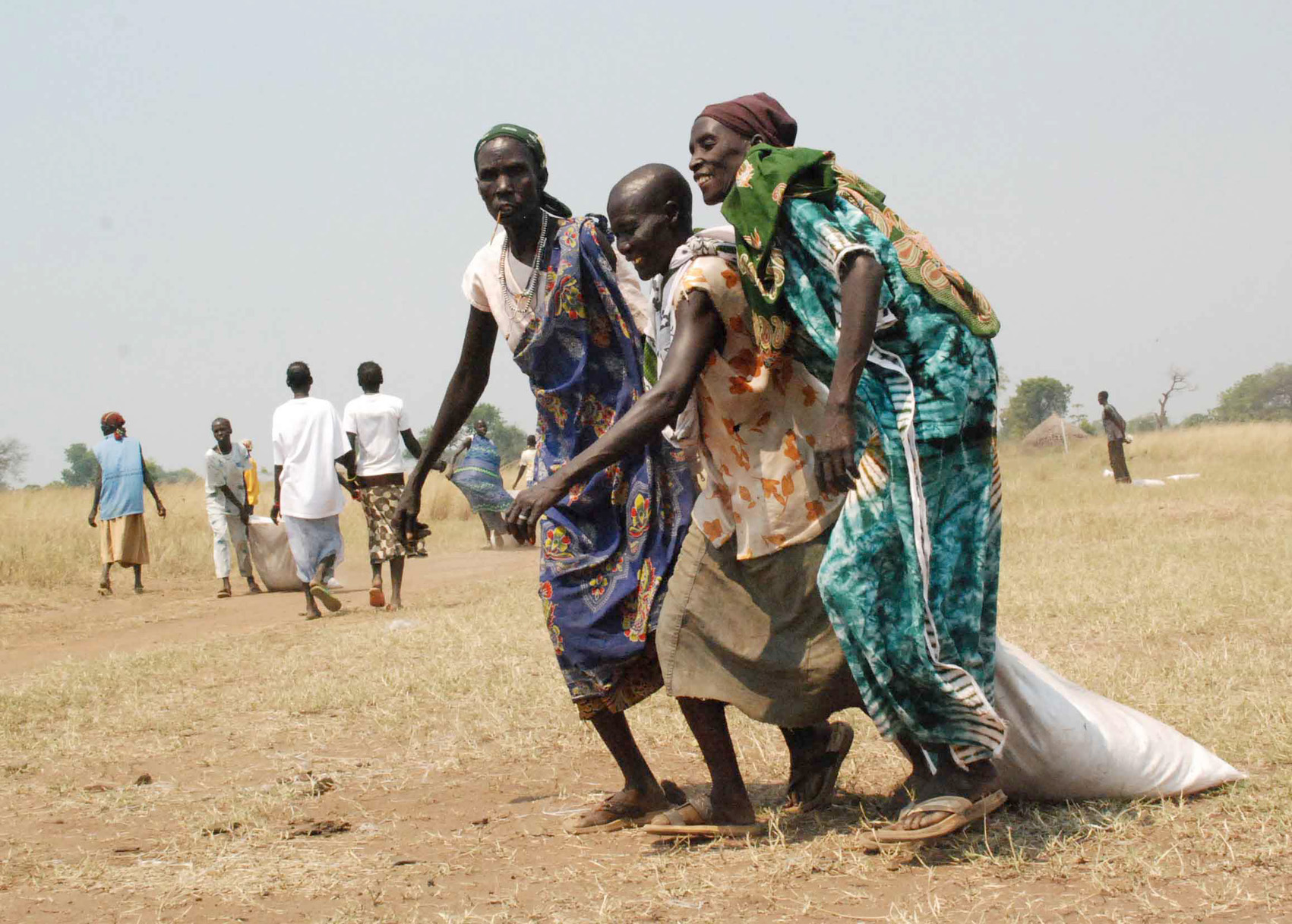 Southern Sudanese women drag bags of grain to a central collection point dropped by WFP chartered airplane in the village of Pochalla, Jonglei state