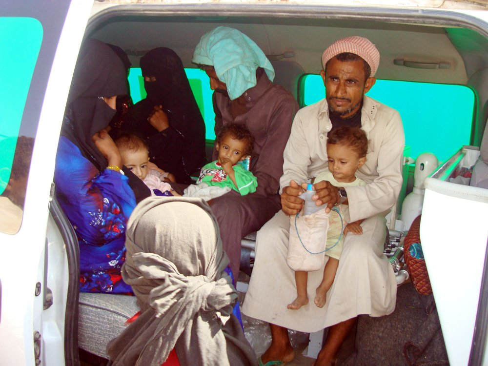 Parents with their severely malnourished babies in a health ministry ambulance leaving al-Mazraq camp for Sanaa-based Sabin Hospital