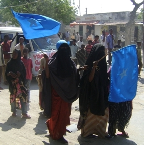 Women wave flags in Somalia's capital, Mogadishu, during a demonstration against Al-Shabab insurgents following the 03 December suicide bombing of a graduation ceremony