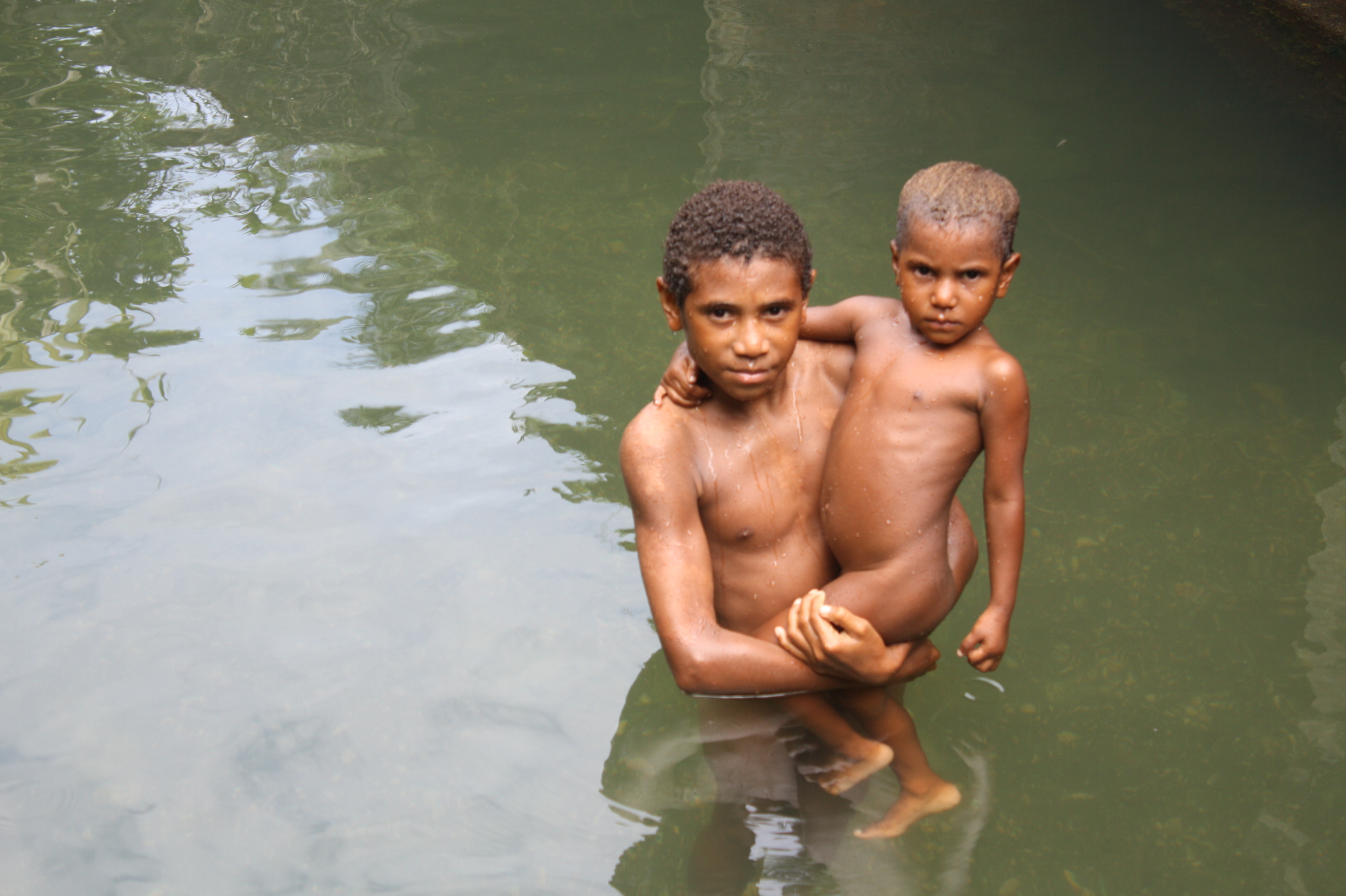 Two boys bathing in a river outside Madang, Papua New Guinea
