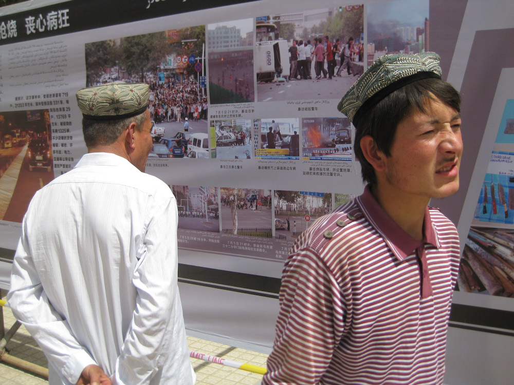 Uyghurs in Xinjiang Province look at posters put up by the Chinese government after the July 2009 protests. The posters show scenes associating Uyghurs with destruction from the protests, or cooperation between Uyghurs and Han Chinese