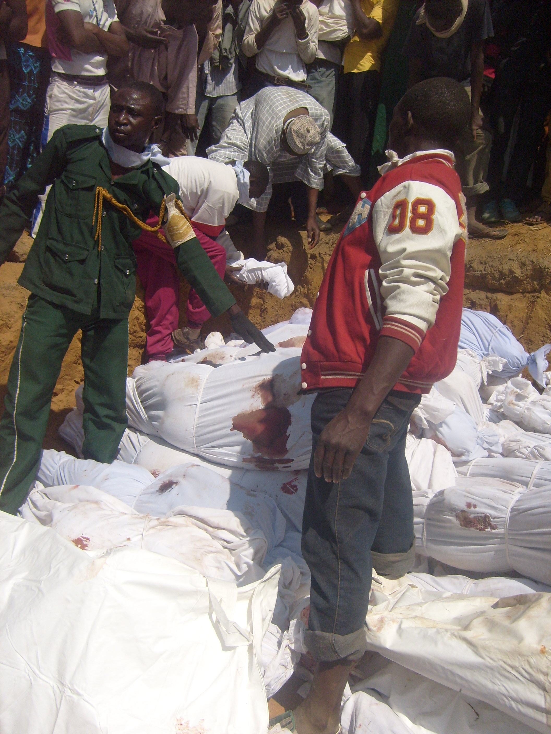 Volunteers arrange dead bodies in a mass grave at Naraguta Cemetery along Bauchi Road in northern part of Jos on Thursday