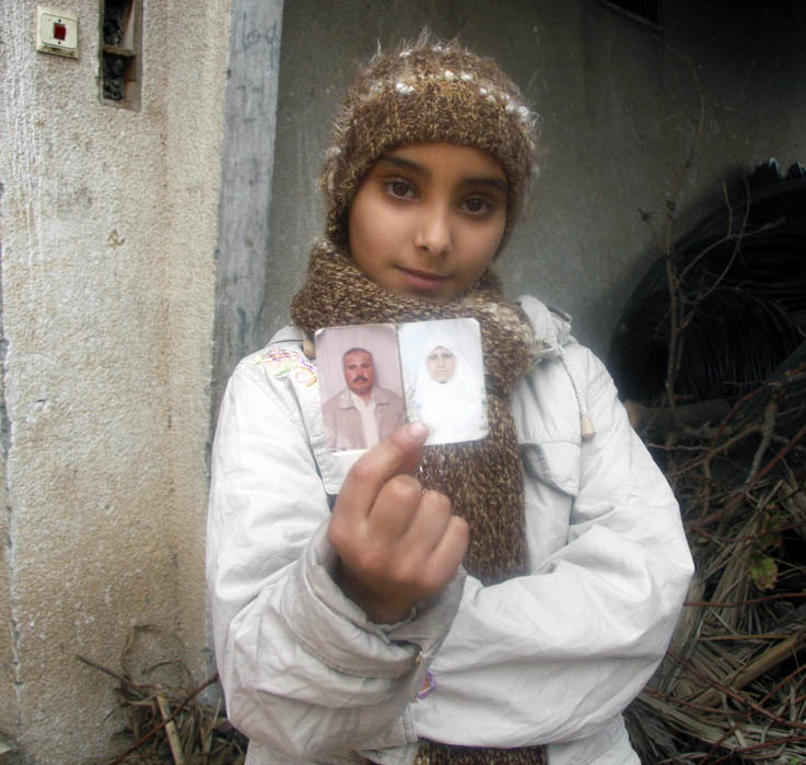 Mona al-Samouni, 12, show a photos of her parents who she witnessed being killed in Israel's war in Gaza in January 2009