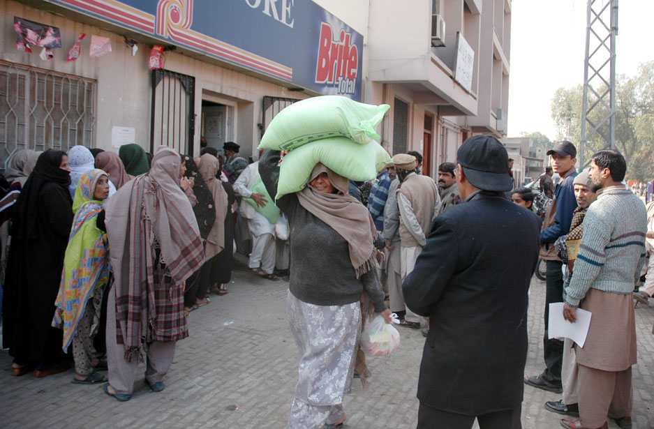 A woman carries home sacks of wheat flour. Pakistanis consume 22 million tons of wheat every year