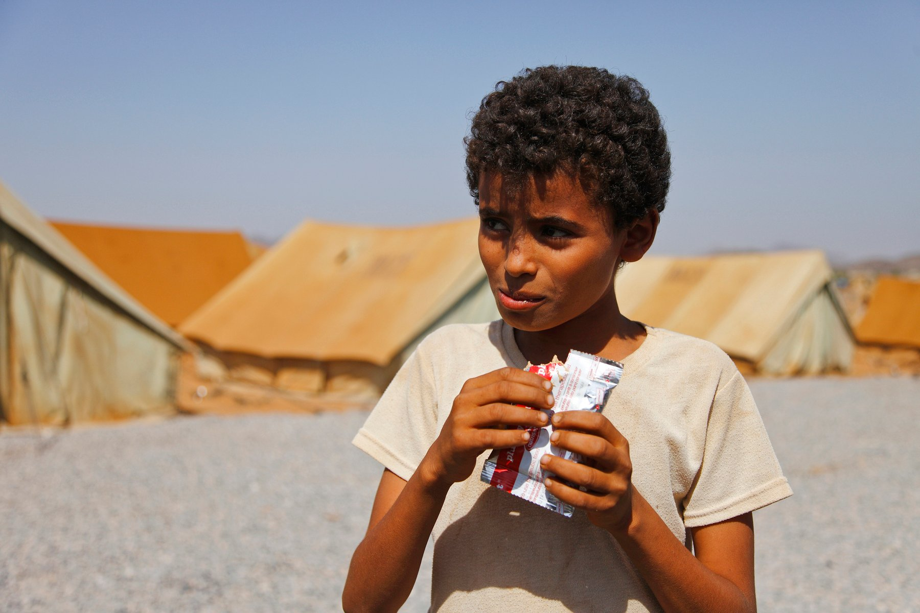 A boy in Mazrak IDP camp in north-west Yemen eats Plumpy'nut, a peanut-based food used in famine relief