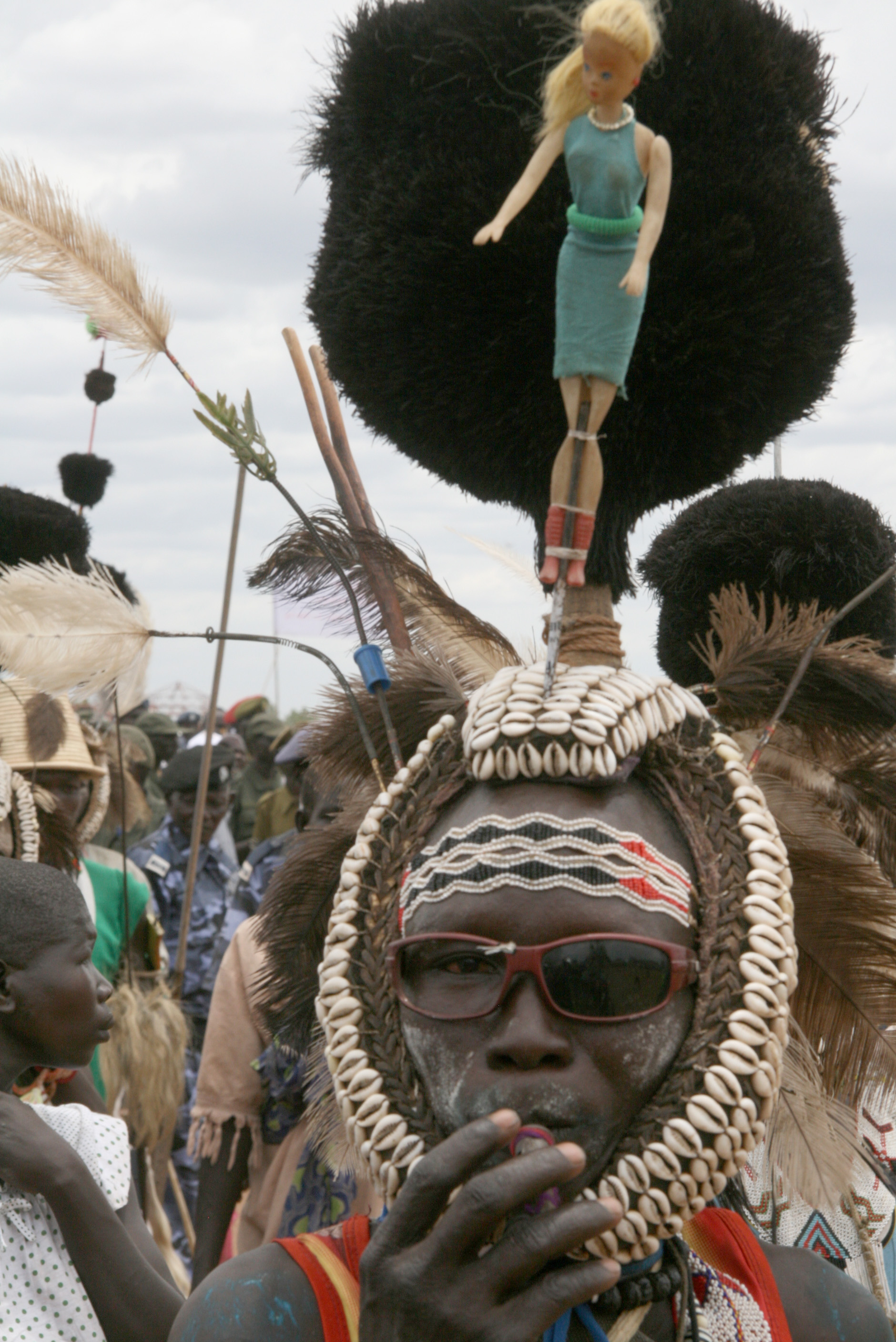 A Toposa man taking part in an election rally at Torit, eastern Equatoria, incorporates a doll into his traditional head gear