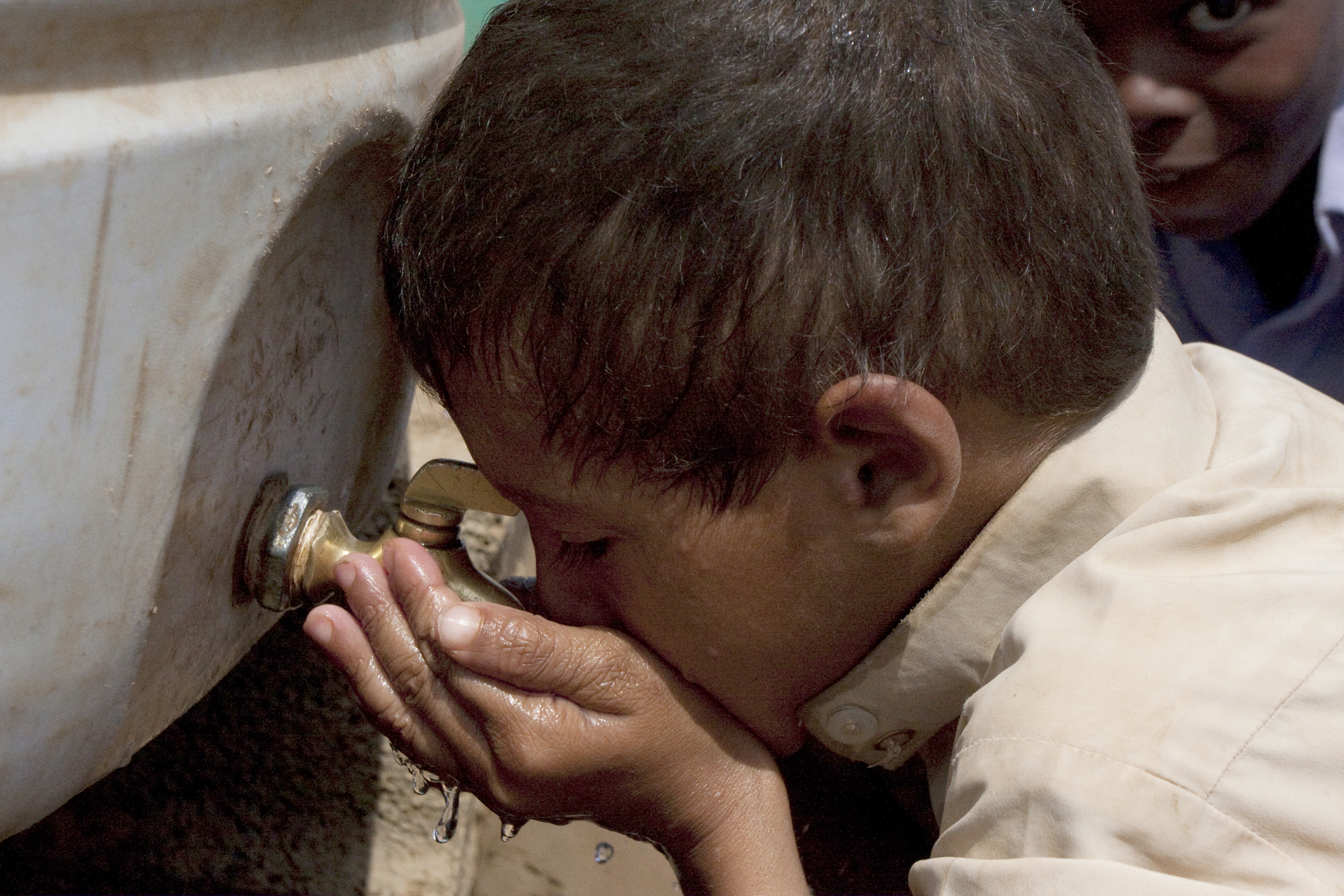 A boy drinks water from a large water tank at Mazraq camp in Hajjah province. The water is delivered by truck to the camp