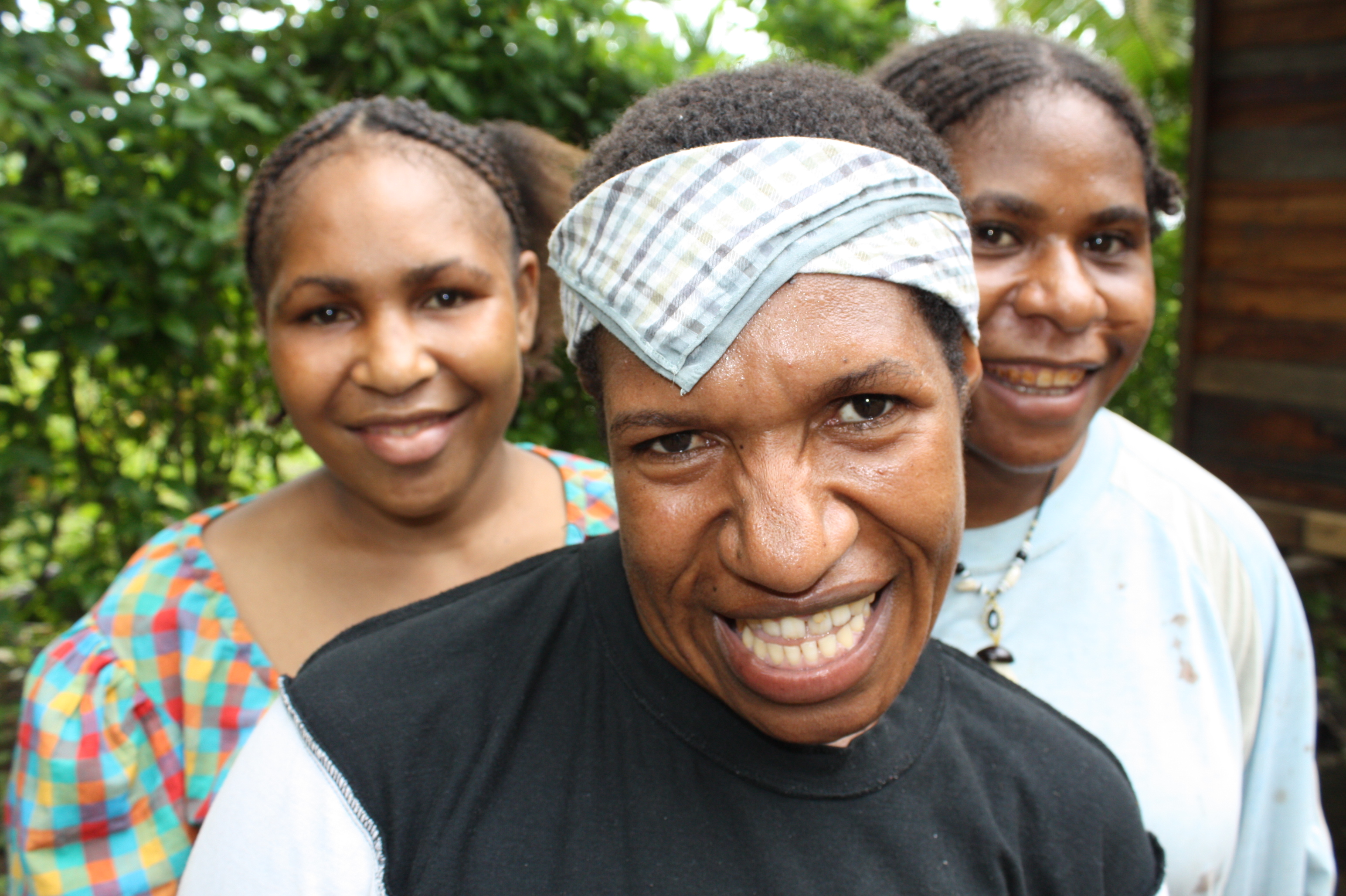 Three women smile to the camera in Madang, Papua New Guinea