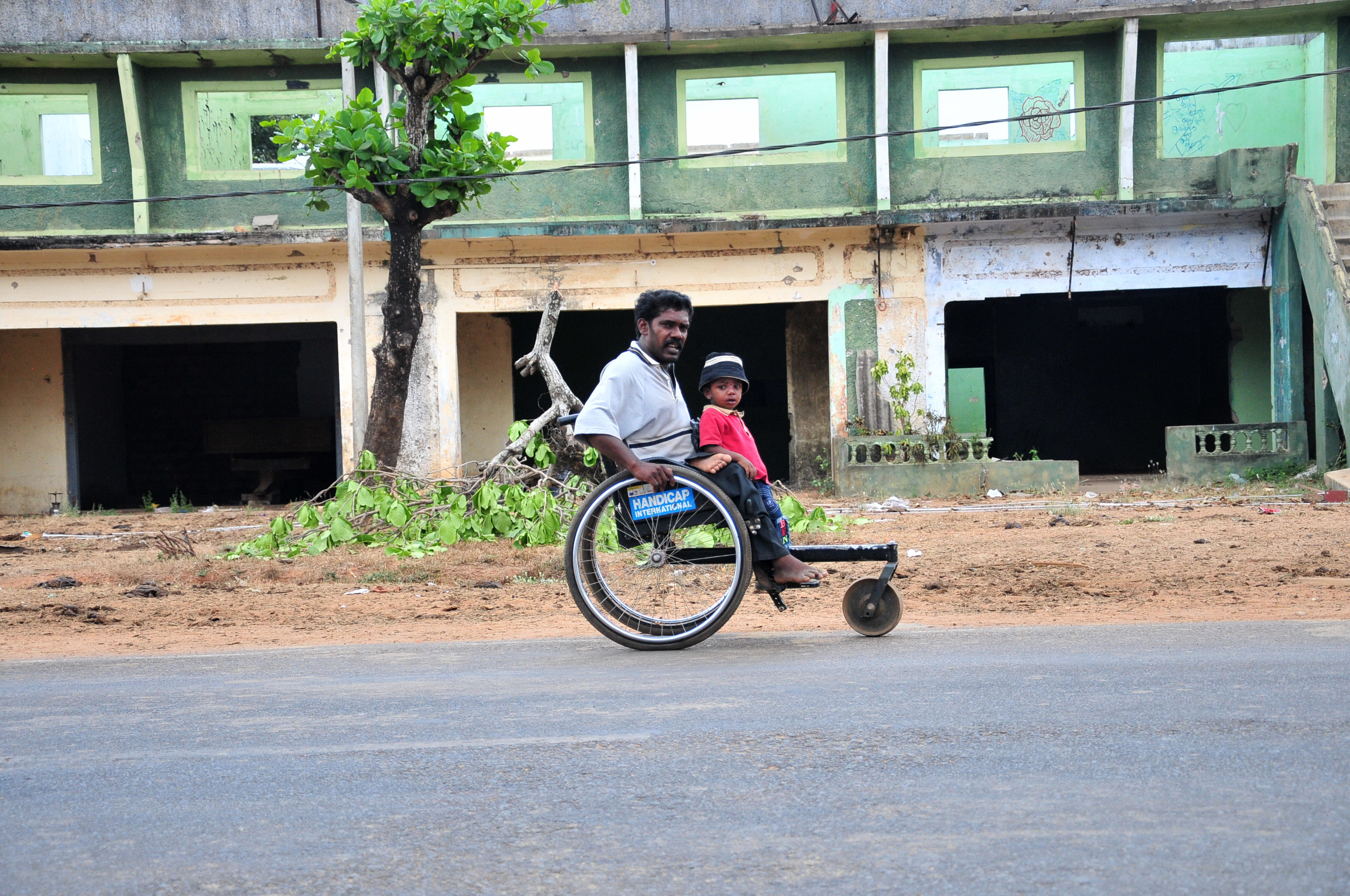 A man in a wheelchair moves along the A9 near Paranthan. Thousands of IDPs have returned to the area more than 10 months after the conflict was officially declared over