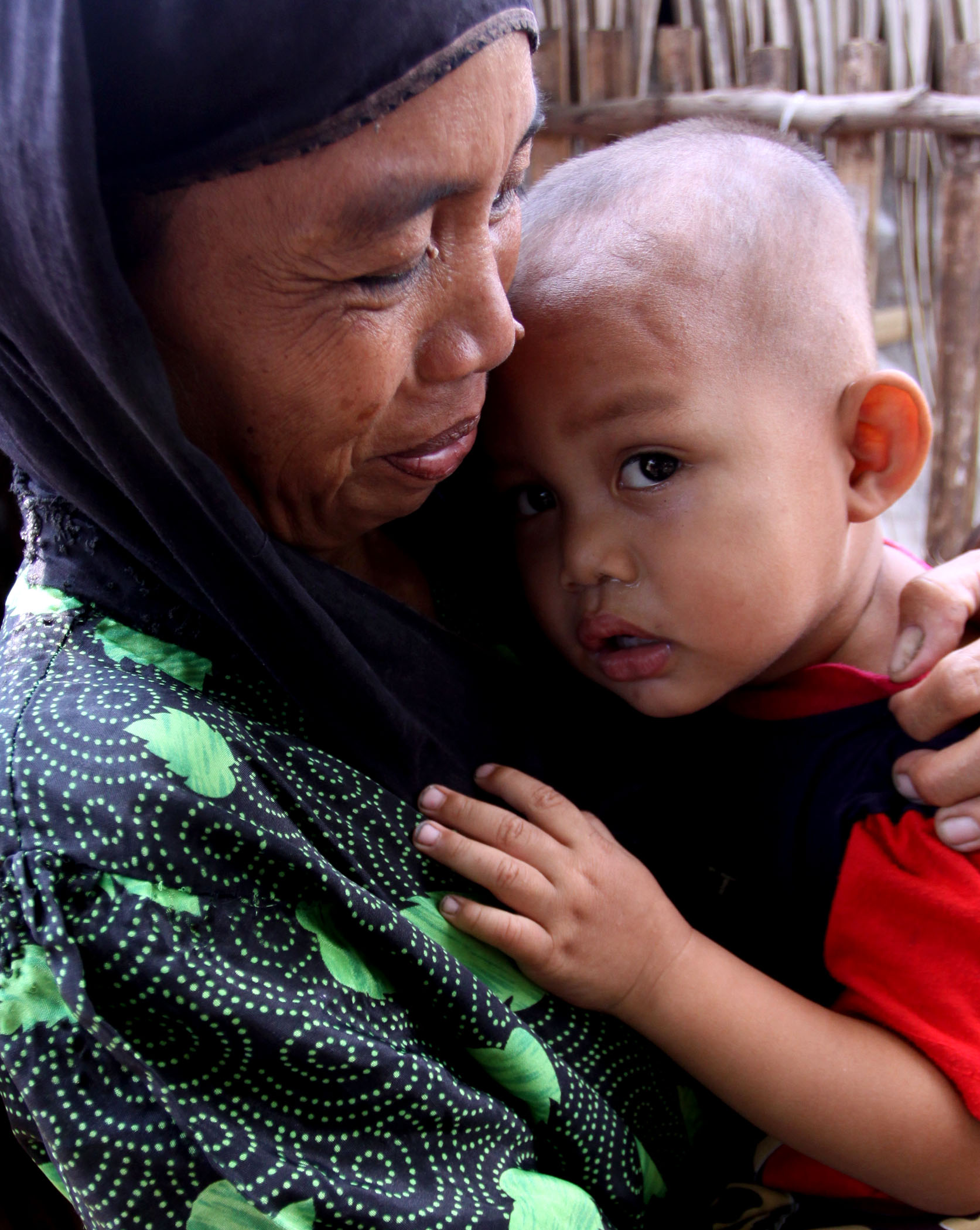 A Muslim woman carrying her toddler at an evacuation centre in the southern Maguindanao Province. The government and the separatist Moro Islamic Liberation Front (MILF) have agreed to facilitate the quick return over tens of thousands of people displaced
