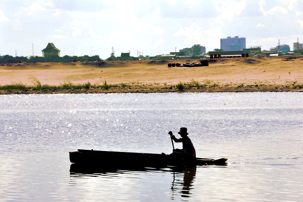 A woman paddles a small fishing boat in a downtown lake Phnom Penhn now being drained by developers - part of dodgy deal to make room for a high end Korean-built residential community