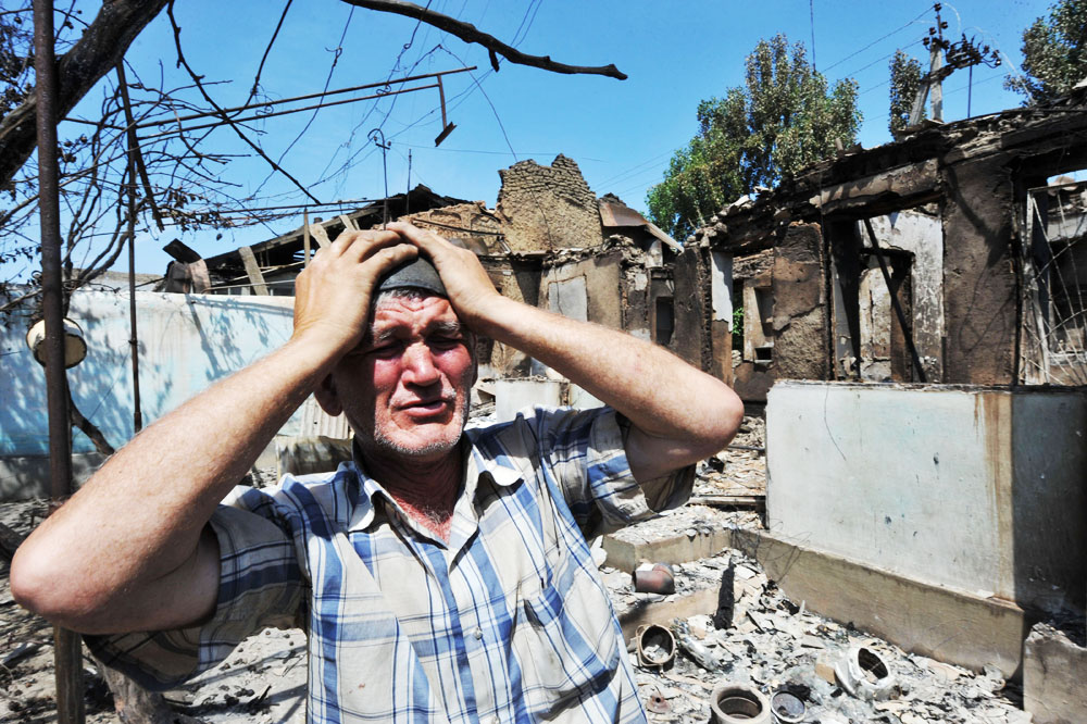 An ethnic Uzbek holds his hands to his head as he stands beside the ruins of his home, destroyed in the violent clashes that began on 10 June 2010 between Kyrgyz and Uzbeks in the city of Osh, Kyrgyzstan