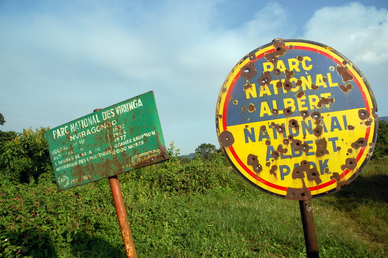 A bullet-scarred sign marks the entrance to a national park in DRC