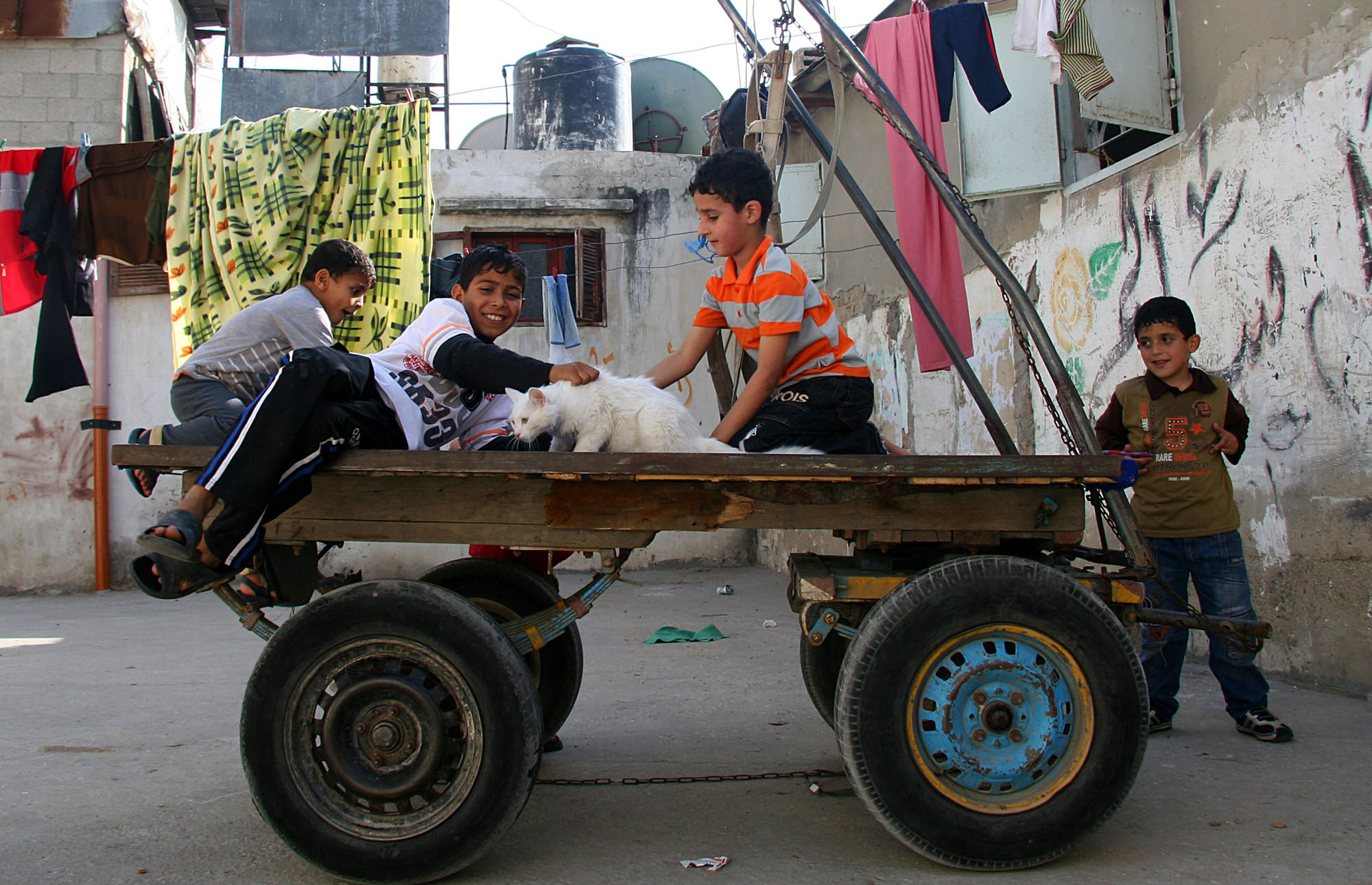 Palestinian refugee children play on a cart outside their houses in Jabalia refugee camps, north the Gaza strip
