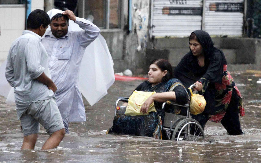 Lahore resident Jamila Hasan and her disabled daughter negotiate their way across a flooded street