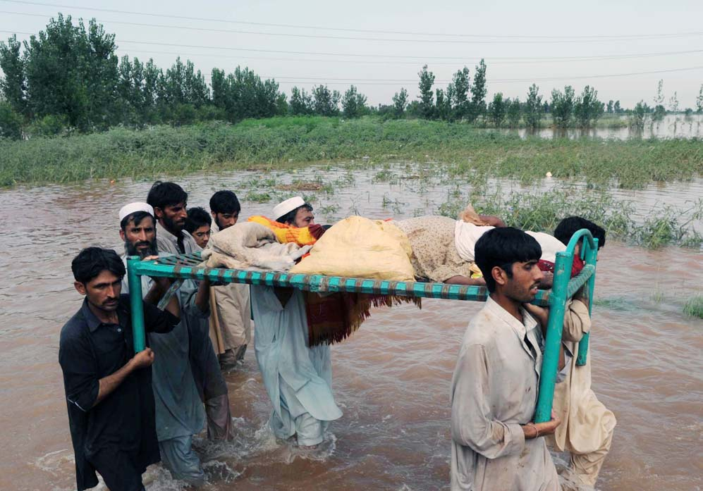 Flood victims in Khyber-Pakhtunkhwa carry an injured relative past destroyed fields