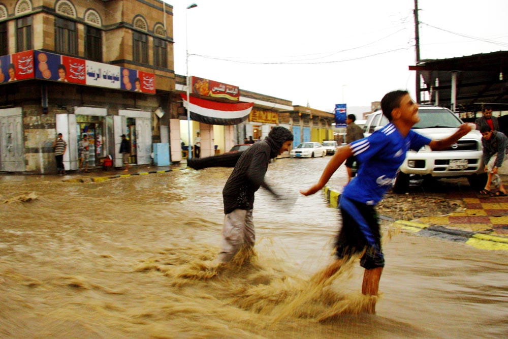 Children play in the flooded streets of Sana'a, the Yemeni capital, while the government fails to harvest the precious rainwater