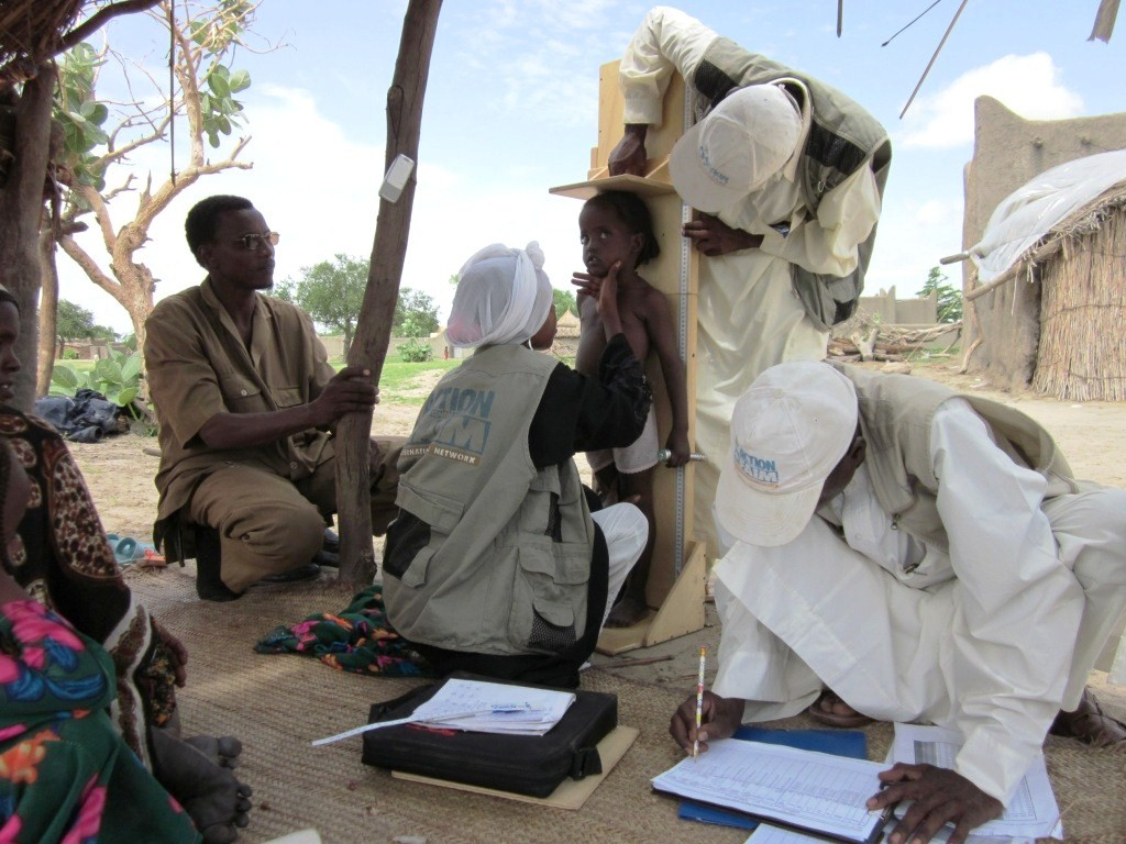 Aid workers and health officials measuring children's height and weight in western Chad