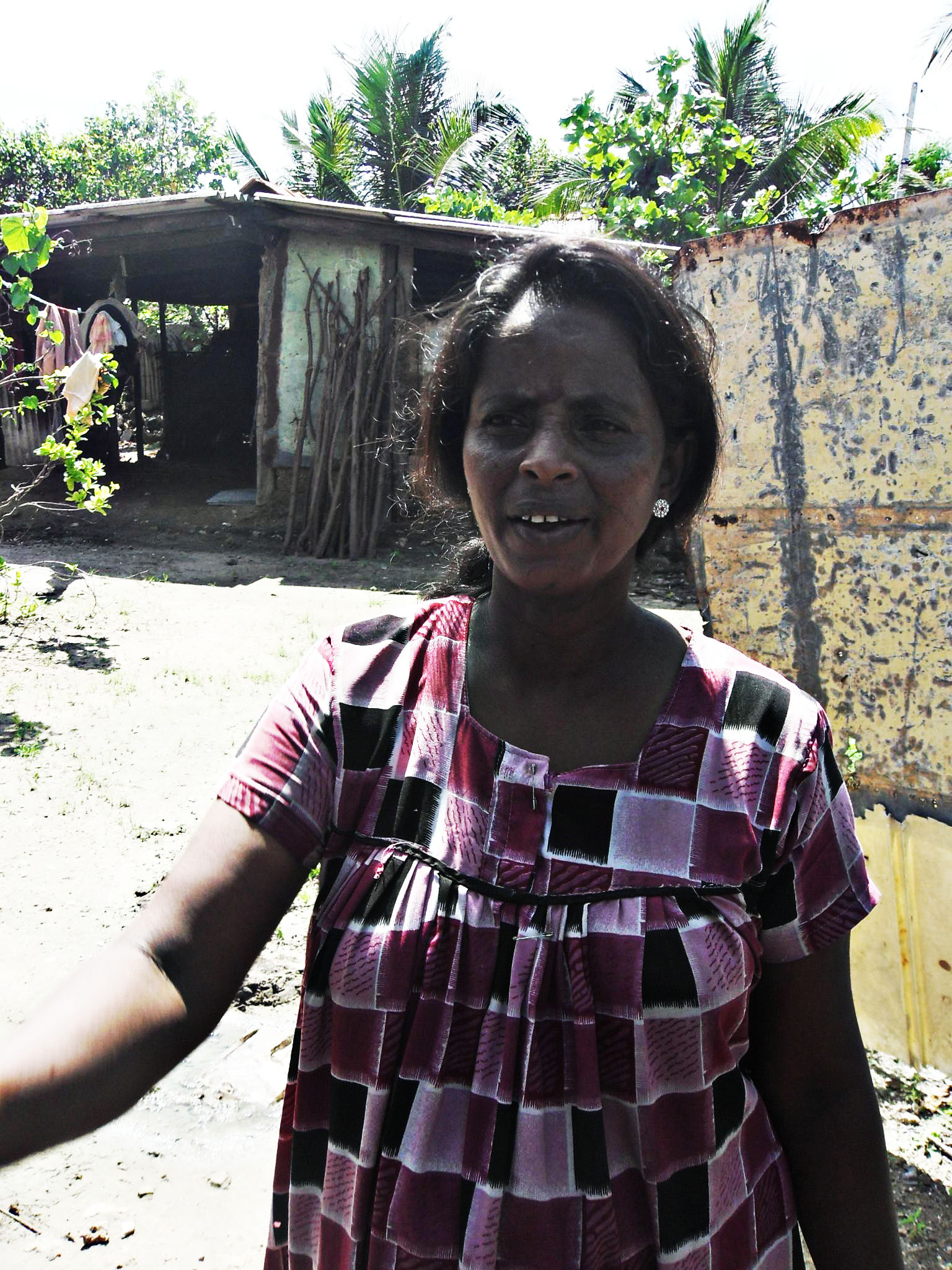 A woman outside her home in northern Sri Lanka. Recent returnees claim that the are still struggling to normalize their lives more than 15 months after the war was declared over