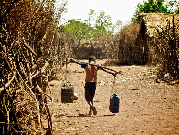 A boy carrying water at Shimelba refugee camp