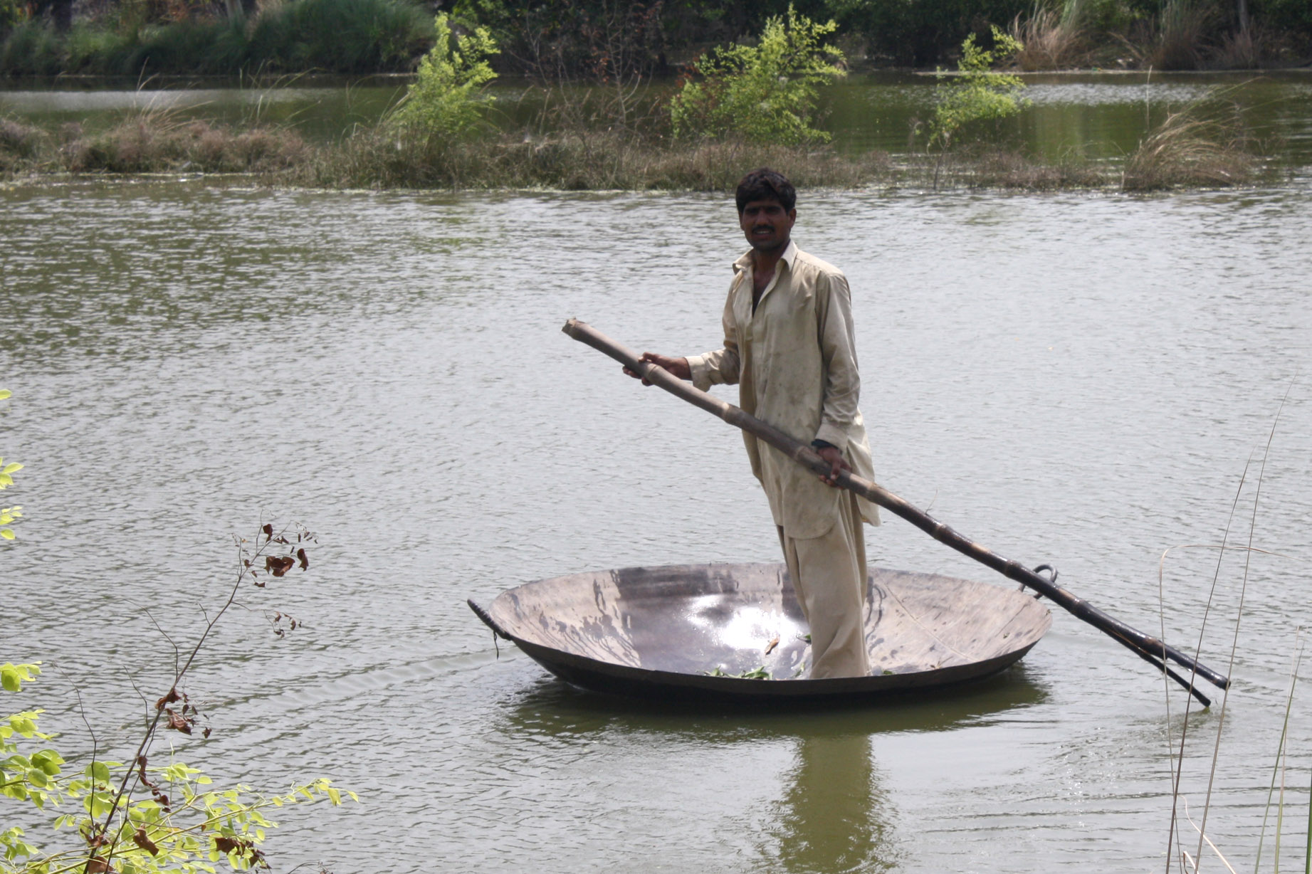 A man uses a large cooking pan as a boat near Reikhbaghwala village, Rajanpur district in Punjab, Pakistan