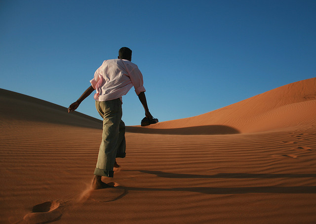 Man walking across a sand dune in Northern Sudan. For generic use