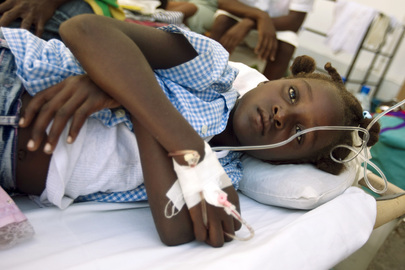 A young girl afflicted with cholera lies in a bed at the crowded St. Nicholas Hospital in Saint Marc, in the Artibonite region of Haiti, where Cuban doctors and doctors with Médecins Sans Frontières are treating those infected