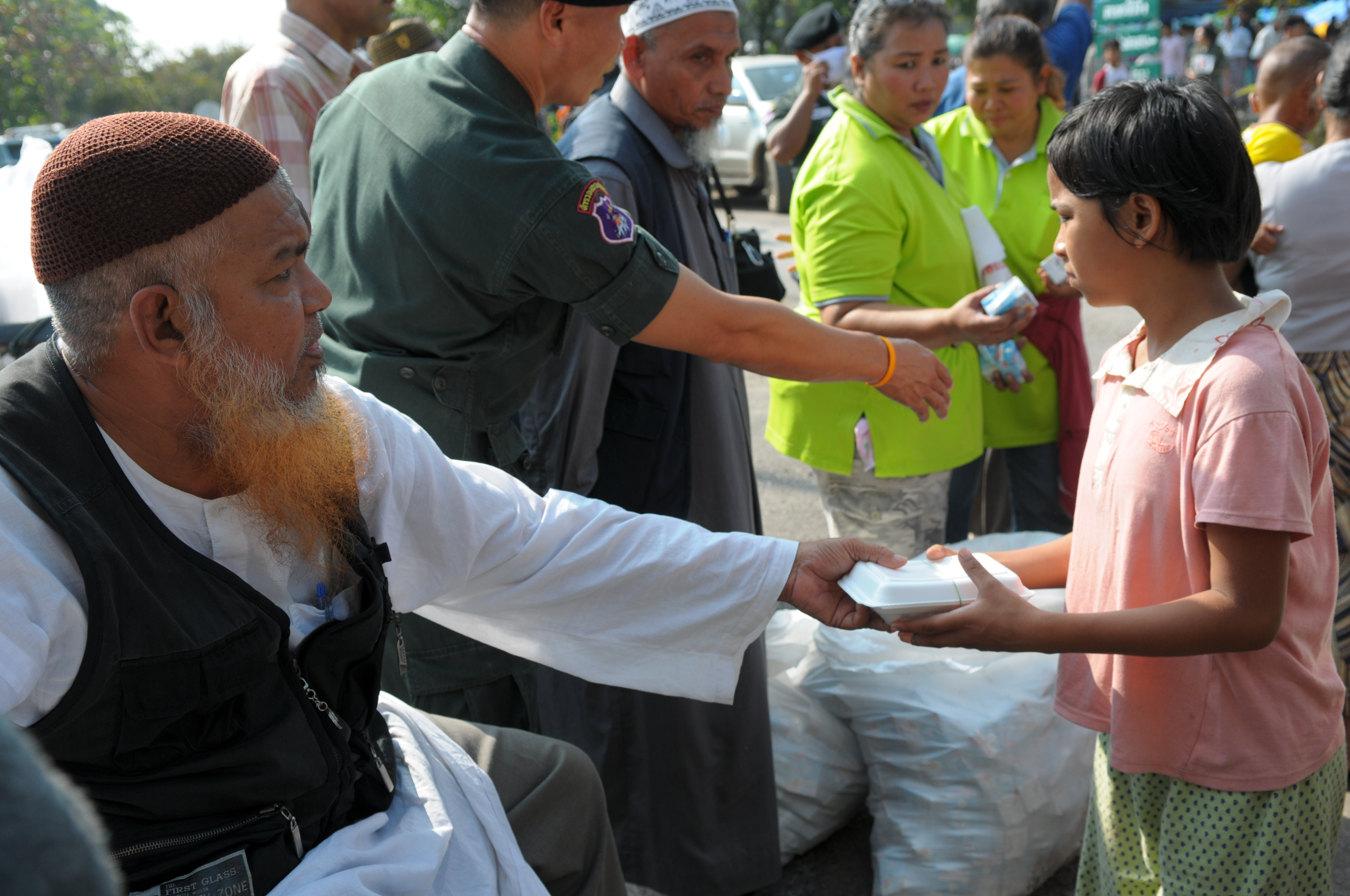 A Muslim volunteer hands out one of some 1500 donated meals to the Muslim refugees at the temporary camp set up at Base 369 of the Thai Border
