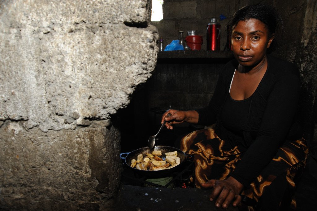 Fatima Maurice, 29, a former member of the Anjouan police, who was dismissed after being part of a rebellion against the government of Comoros, cooking food for her family in a room shared with her four children