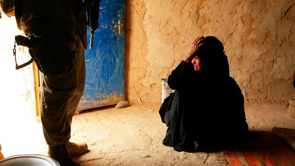 An Iraqi women looks out the door while an U.S. Marine provides security to a U.S. Navy Corpsman in Salah Ad Din, Iraq on May 14, 2008. U.S. Marines and Soldiers are working with Multi-National Forces West (MNF-W) Joint Combat Element in Operation Destroy