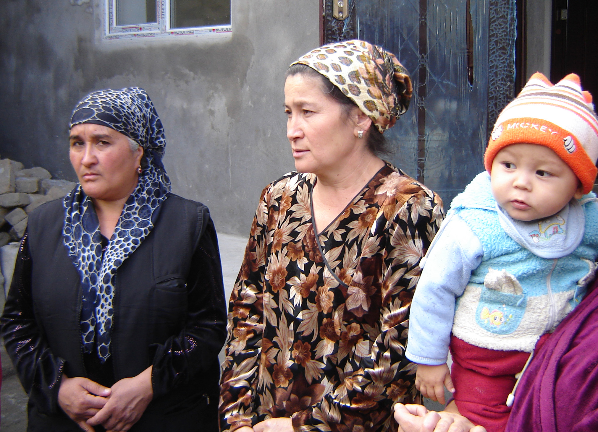Women in Kyzyl-Kyshtak village in the vicinity of the southern city of Osh which saw violent clashes in June that resulted in hundreds of killed, in the background a completed transitional shelter of two rooms