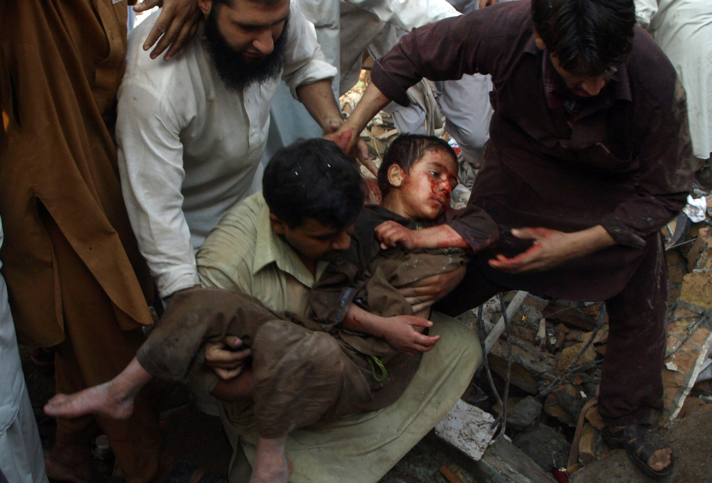 An injured boy is carried out of a busy bazaar in the city of Peshawar after a bombing on October 28th, 2009