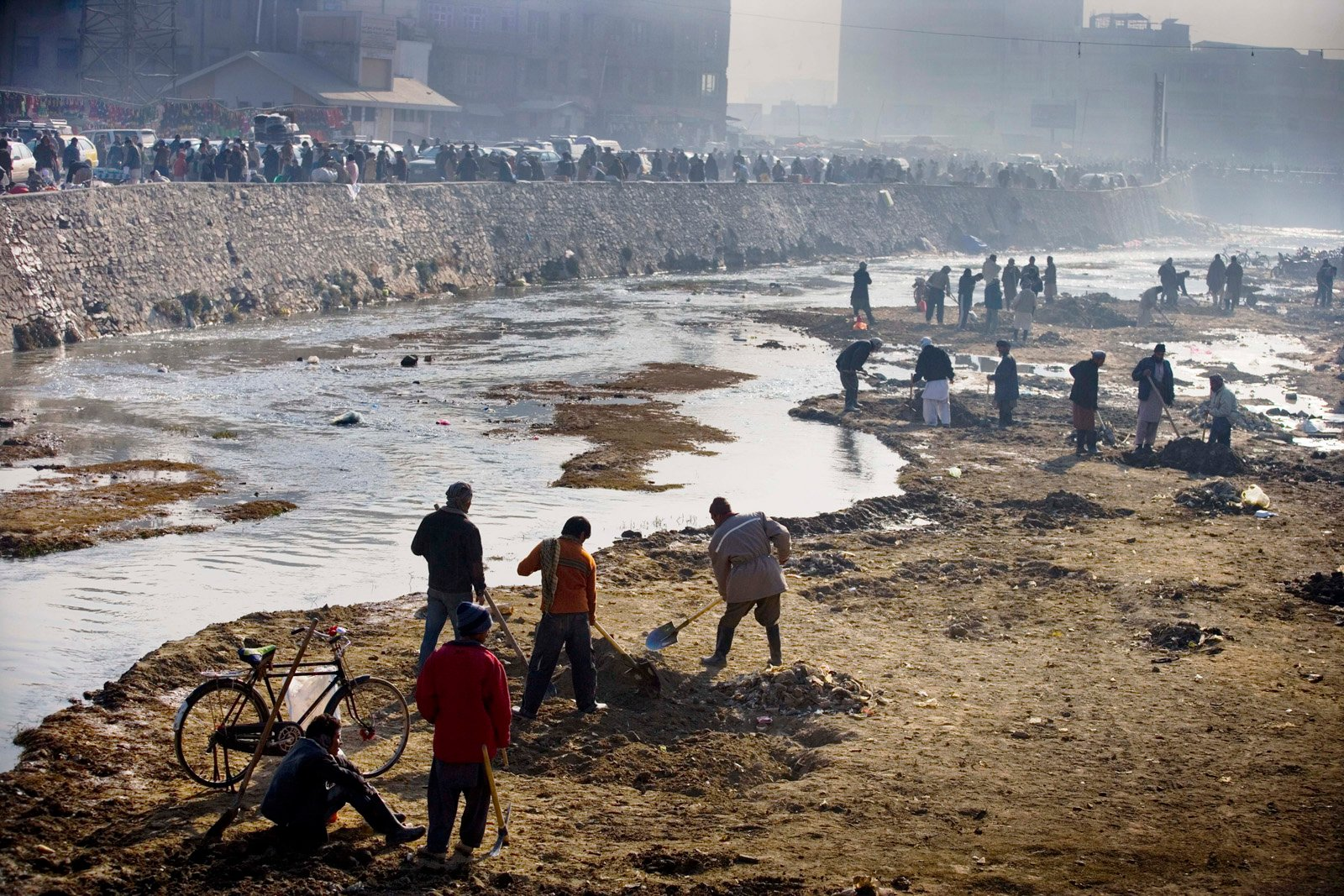 Workers clear out the Kabul river. Kabul 's main river has become increasingly polluted over the last few years, and it is currently being dredged
