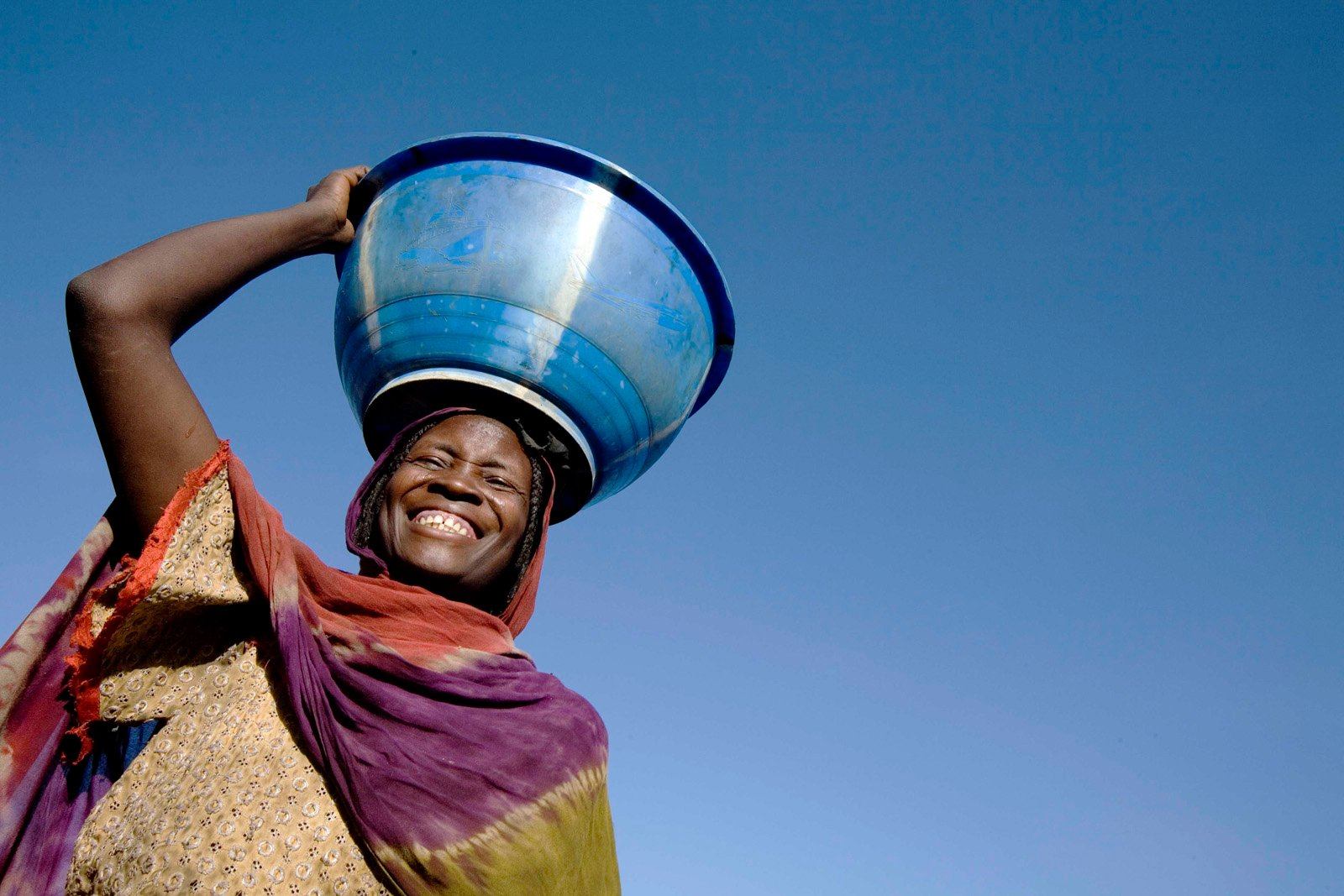 A woman carries water on her head at a settlement for displaced people in Goz Baeda, Eastern Chad