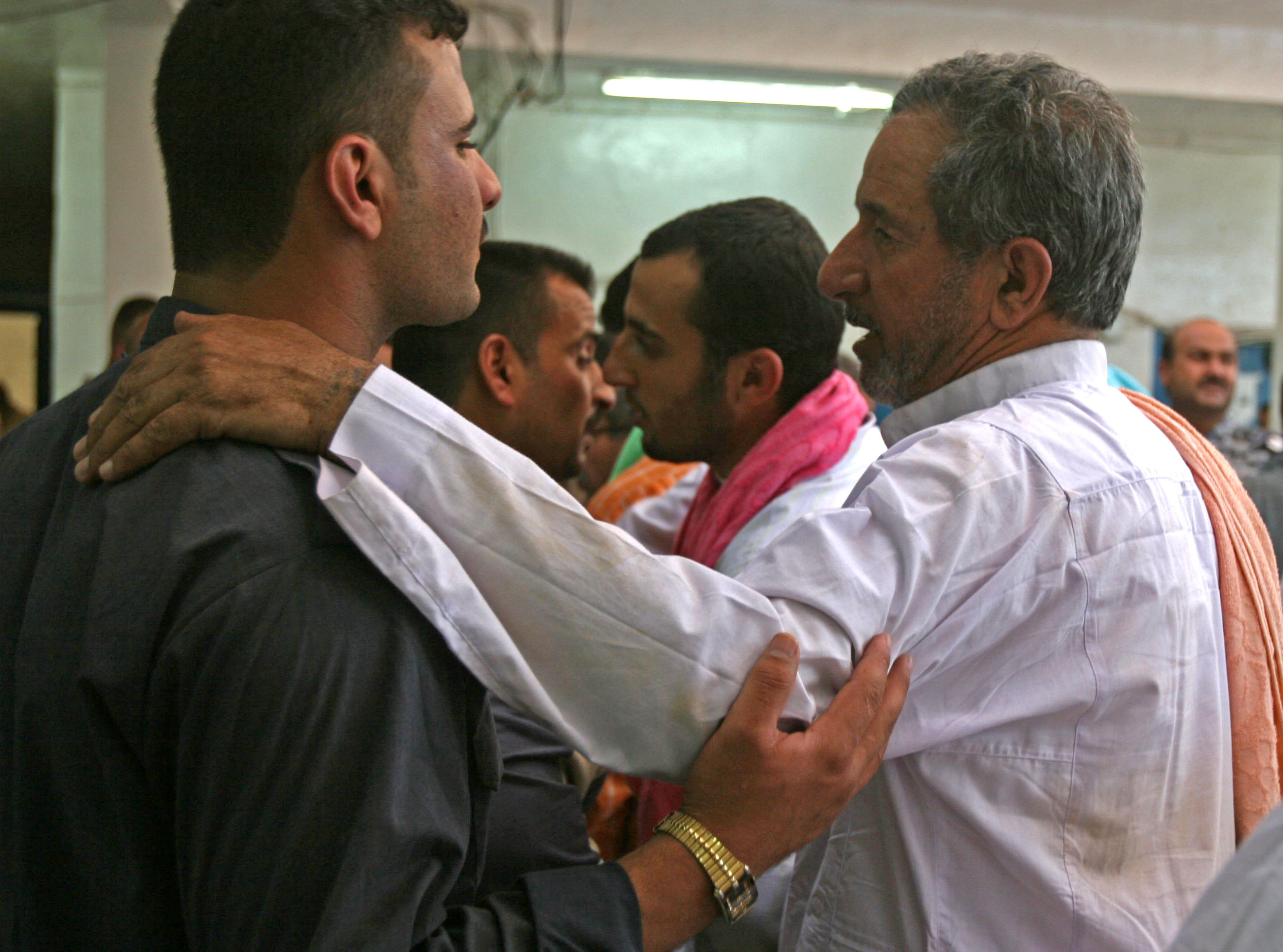 An Iraqi man speaks with an Iraqi Police Officer at the Iraqi Police Station in Karma, before he is released back to his family
