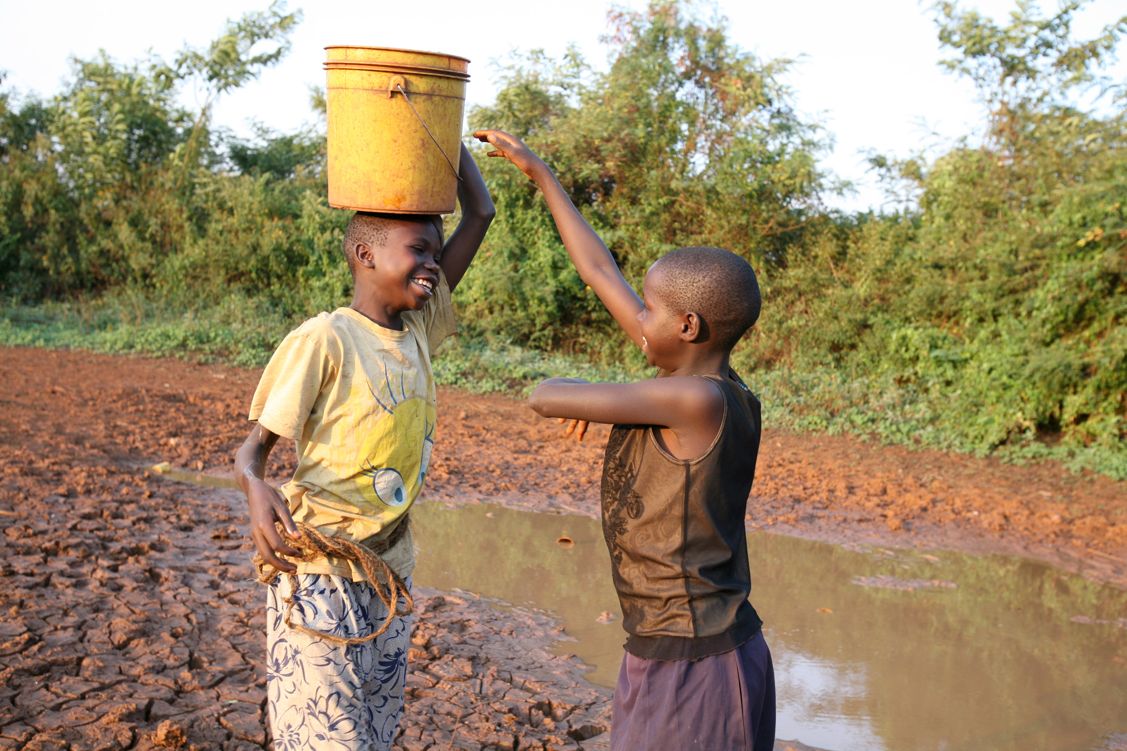 Children play near a dried up water pan in Barchando, Bondo