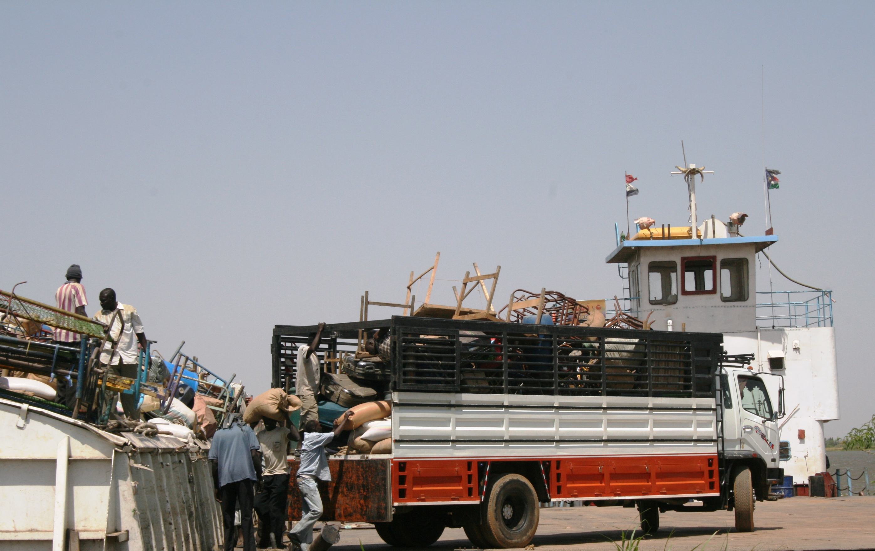 Men load a barge heading to southern Sudan at Kosti Way Station, white Nile State