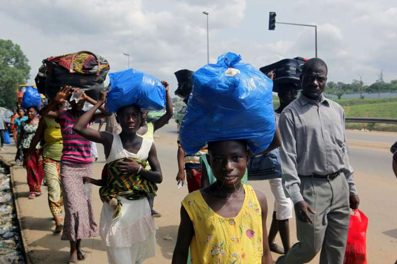Residents of the Abobo suburb carry their belongings as they flee the intense fighting