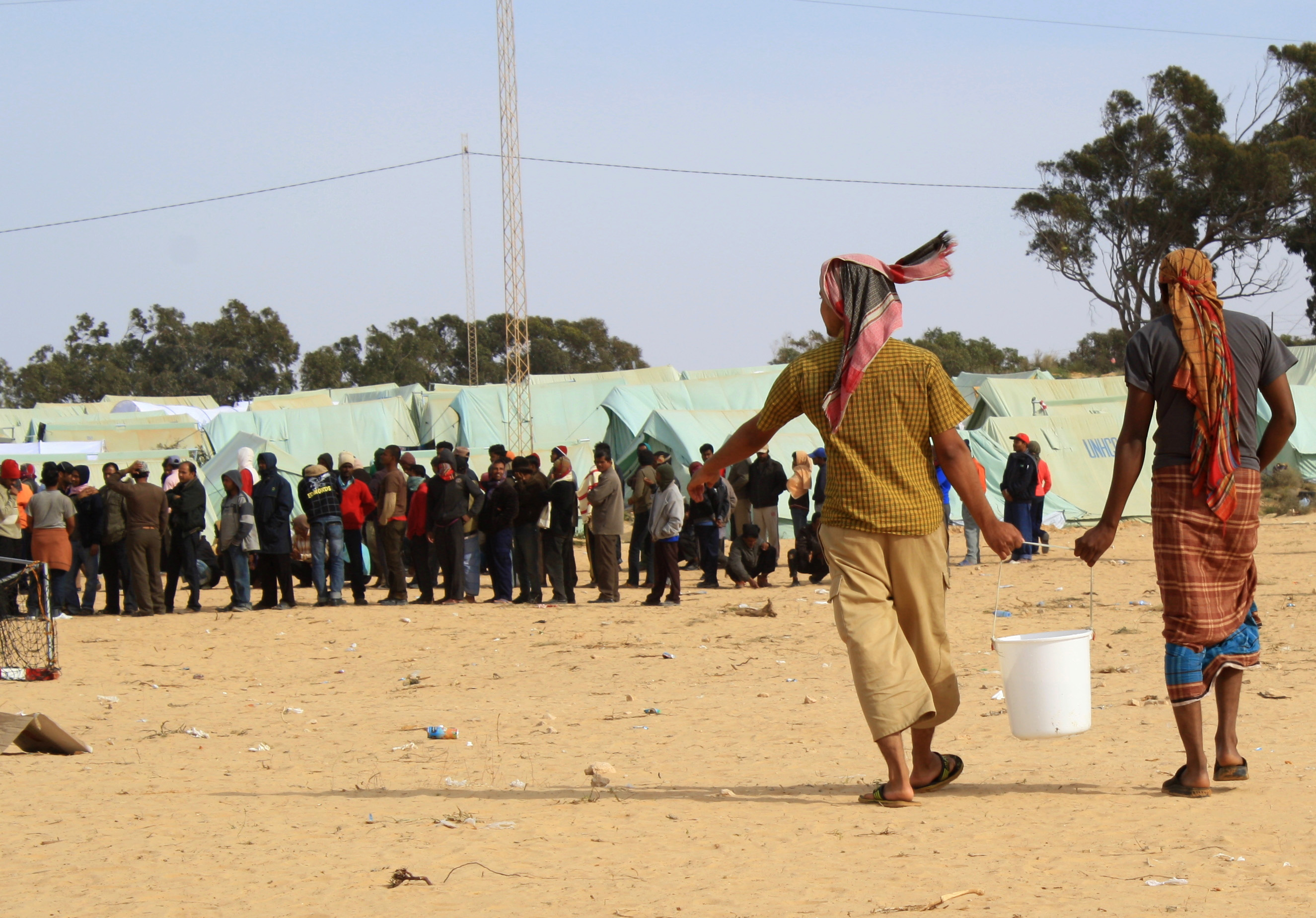 Men carry a bucket of water at Choucha camp whilst others queue for assistance in the background