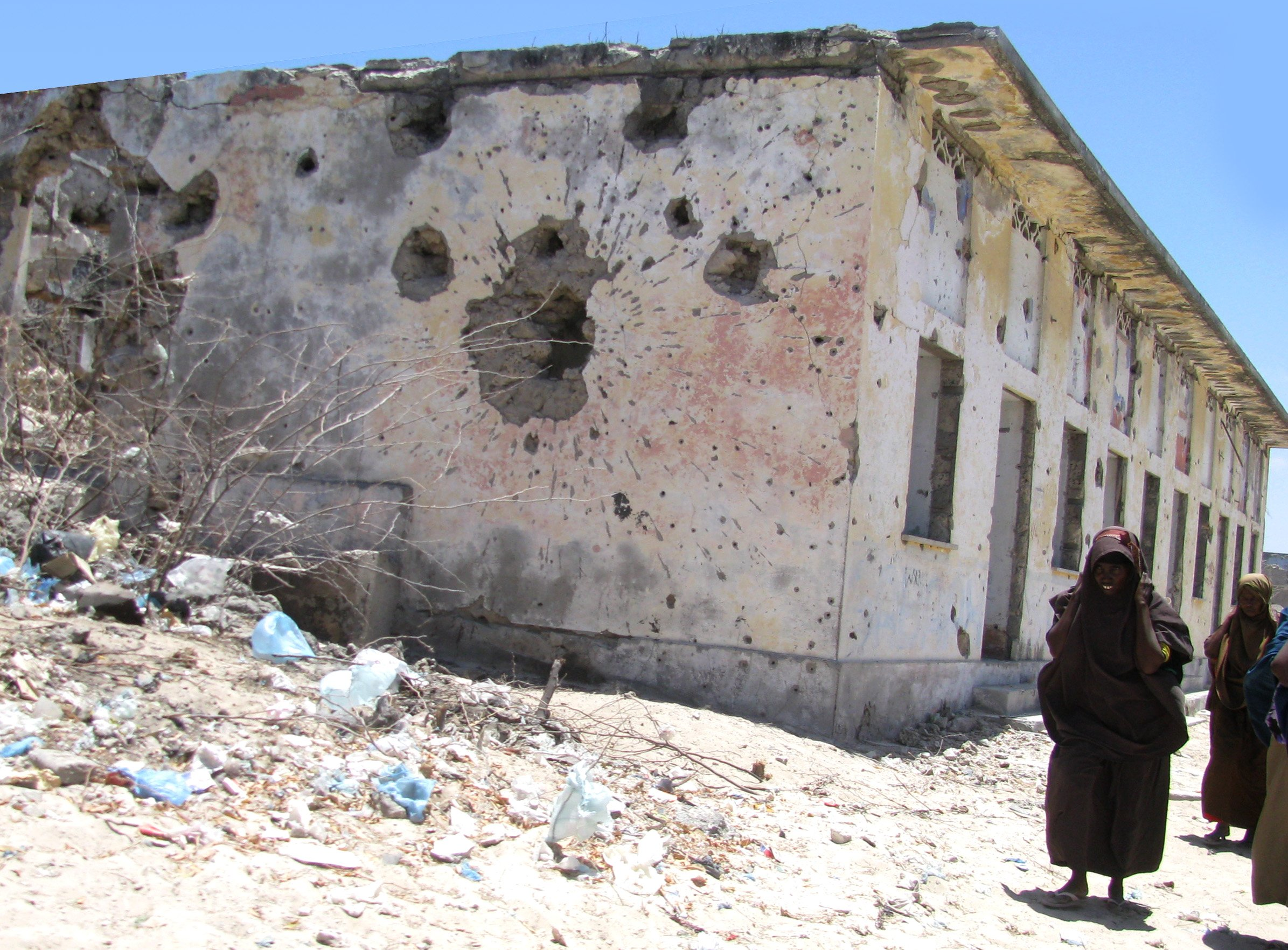 Women walk from Bakara market past a bullet-ridden building in Mogadishu