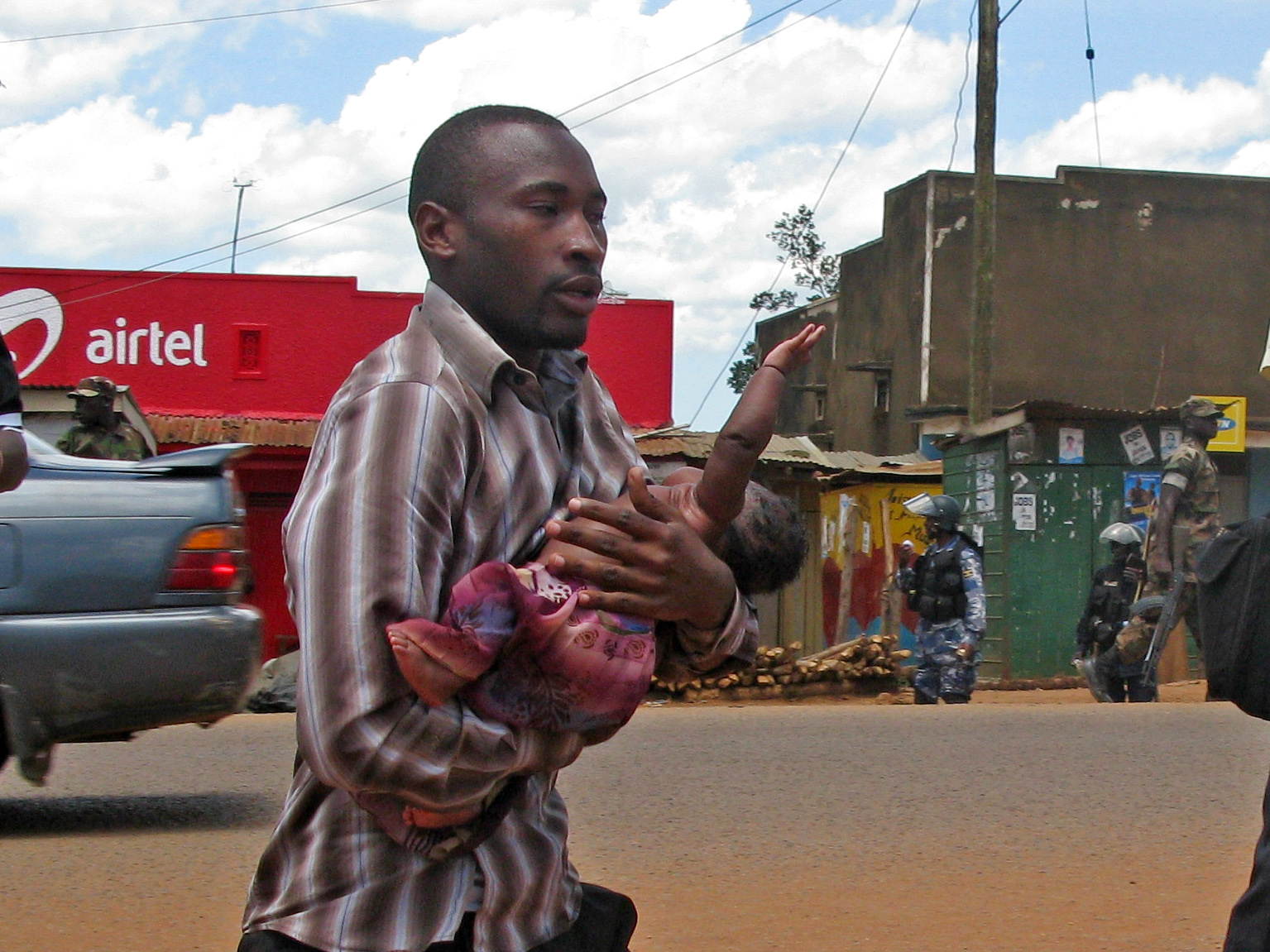 "A man rushes to save a baby suffocating from teargas in Kasangati, a suburb of Kampala, Uganda during ""Walk to Work"" protests by Ugandans over the high cost of living"