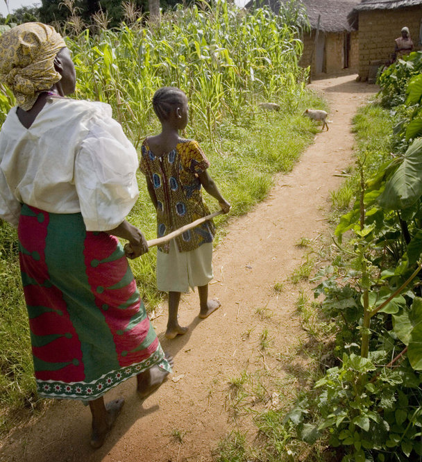 A woman who contracted river blindness many years ago is led along a path by her great granddaughter at her home in Aguna village, Kachia, in Nigeria's Kaduna State