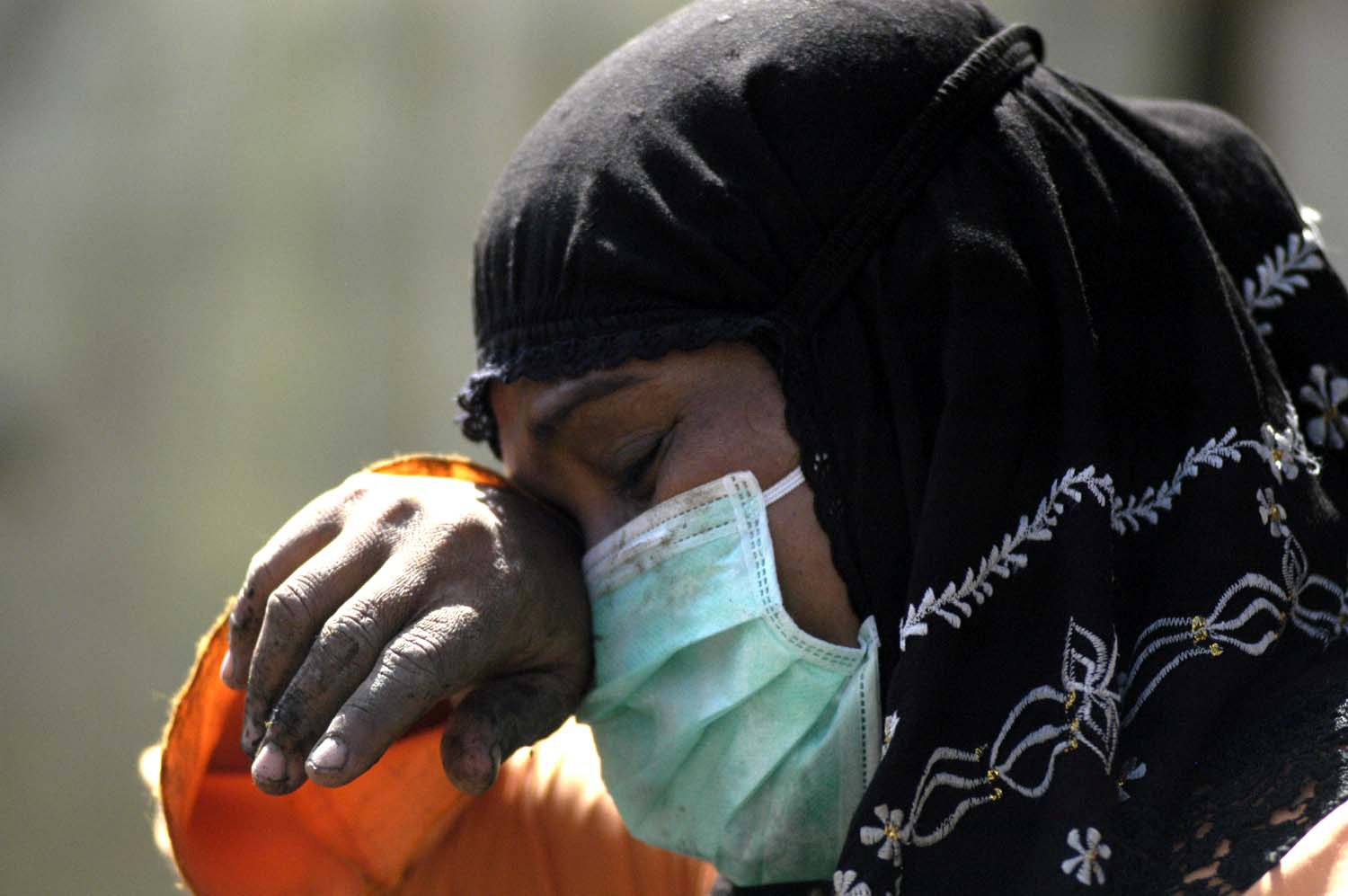 A woman cries while searching for family members amidst the ruins of her collapsed home in Meulaboh, Aceh on 2 January, 2005. Meulaboh, the capital of West Aceh Regency, was one of the hardest hit areas