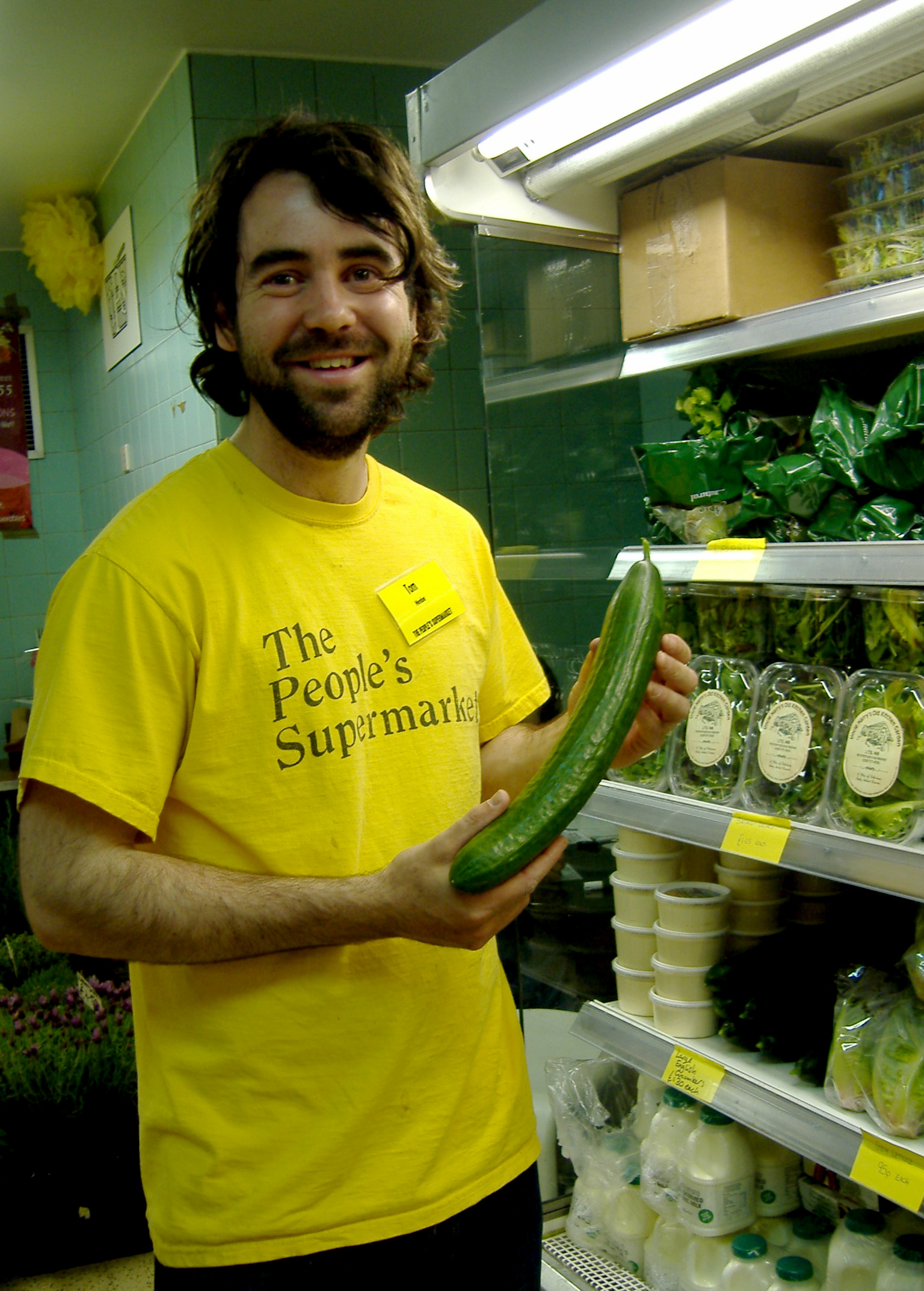 Tom Smith, duty manager at the People's Supermarket, holding a cucumber rejected by a major supermarket on the grounds that it was too big!