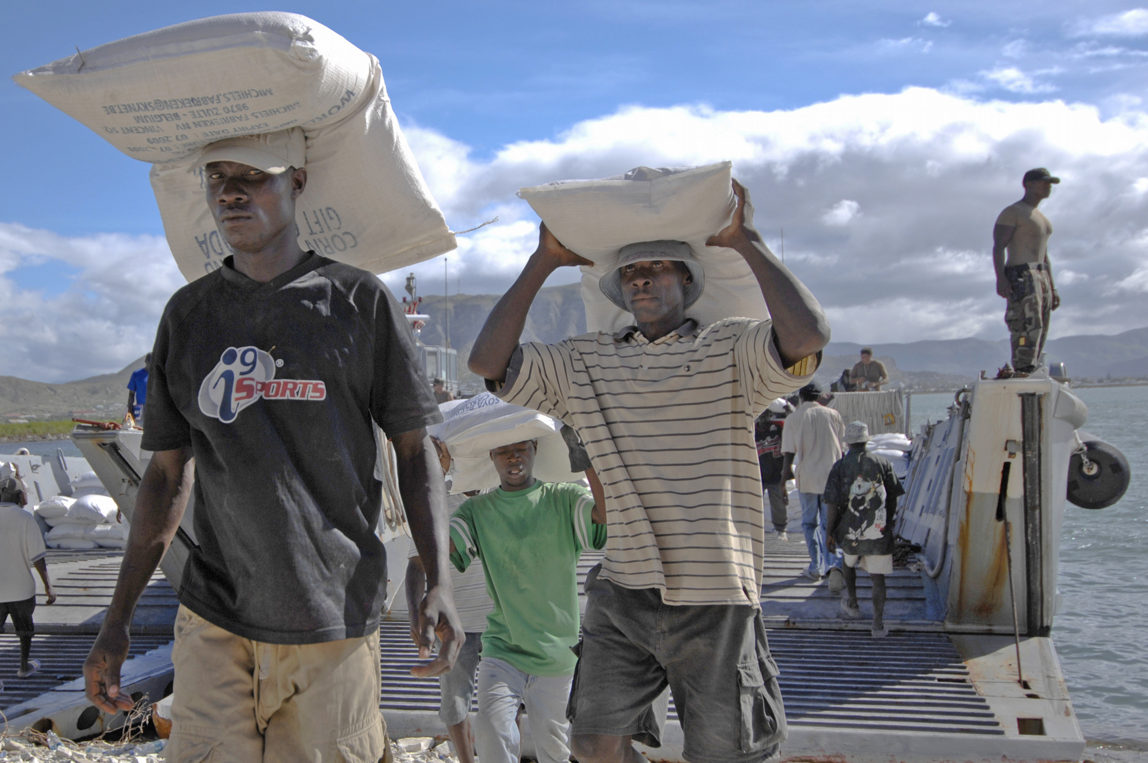 Haitian civilians unload relief supplies from a US Navy ship