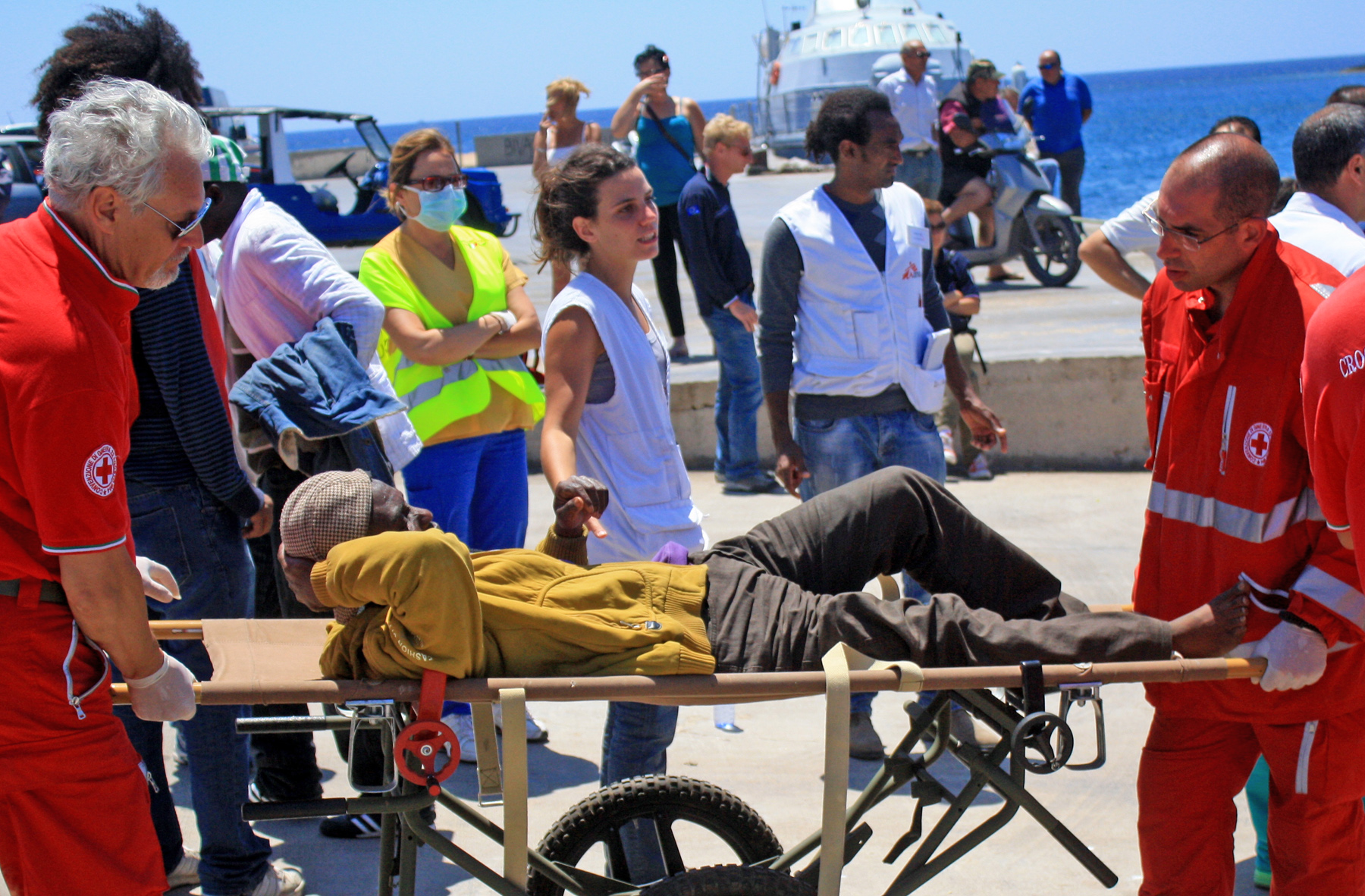 Paramedics from the Italian Red Cross treat an injured migrant worker at Lampedusa's port