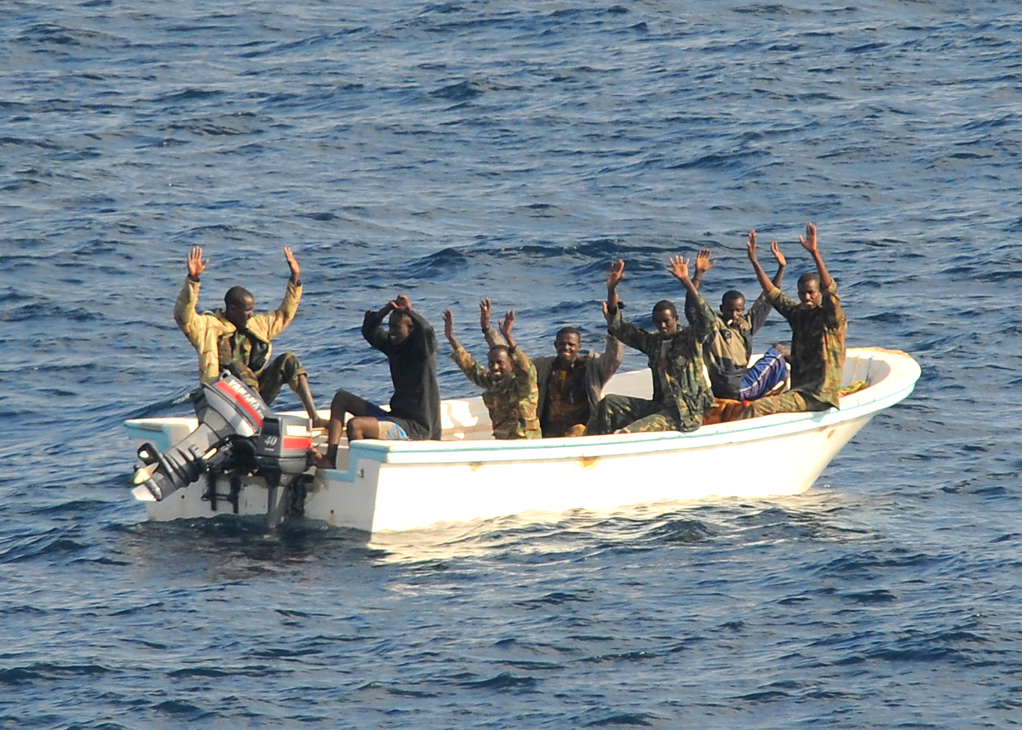 Suspected pirates keep their hands in the air as directed by the guided-missile cruiser USS Vella Gulf (CG 72) as the visit, board, search and seizure (VBSS) team prepares to apprehend them. Vella Gulf is the flagship for Combined Task Force 151, a multi-