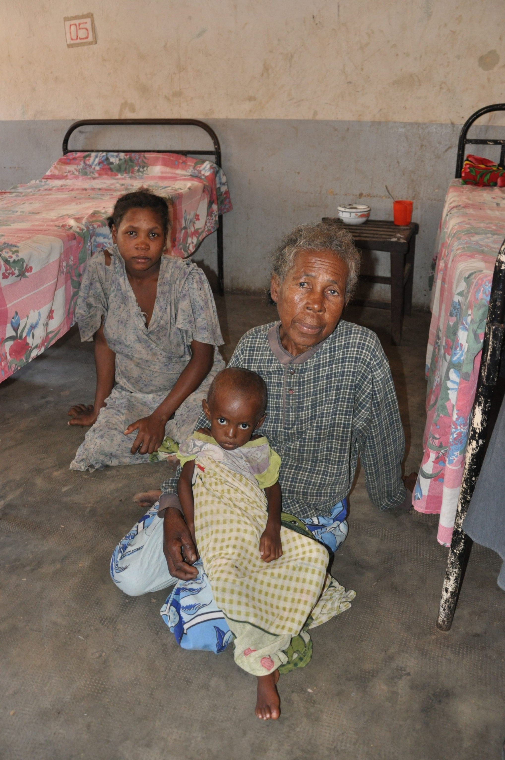 Three-year-old Lambo, who weights just 5.8 kilos, with his grandmother and mother at the Centre for the Treatment of Acute Malnutrition with Complications (CRENI) in Amboasary Sud, southeastern Madagascar